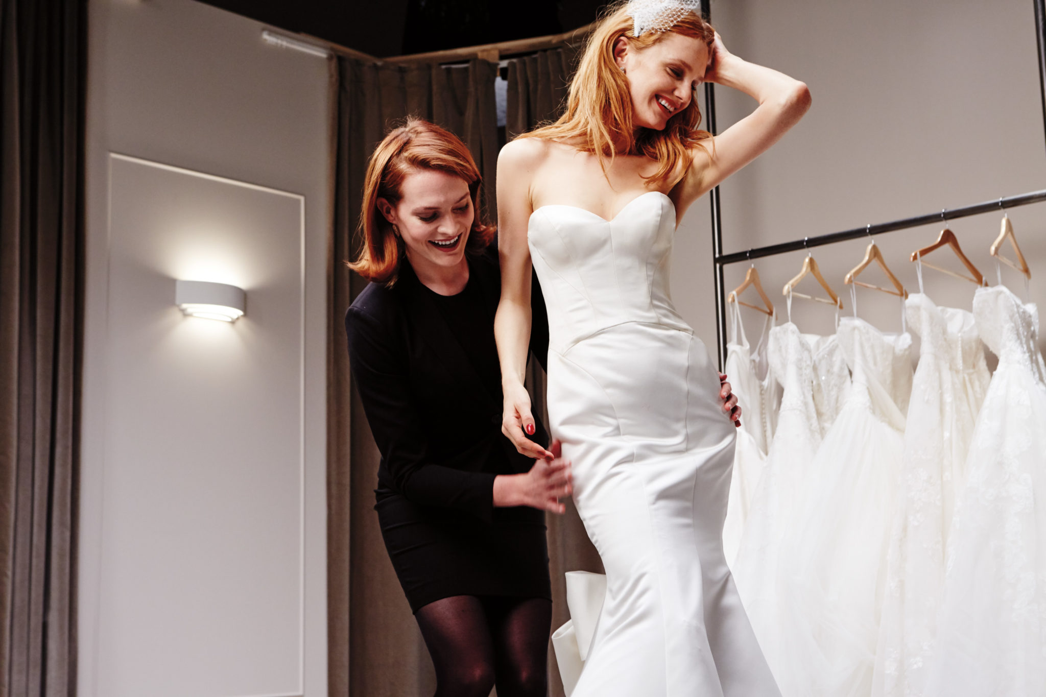 Alterations expert fitting a bride in a wedding dress