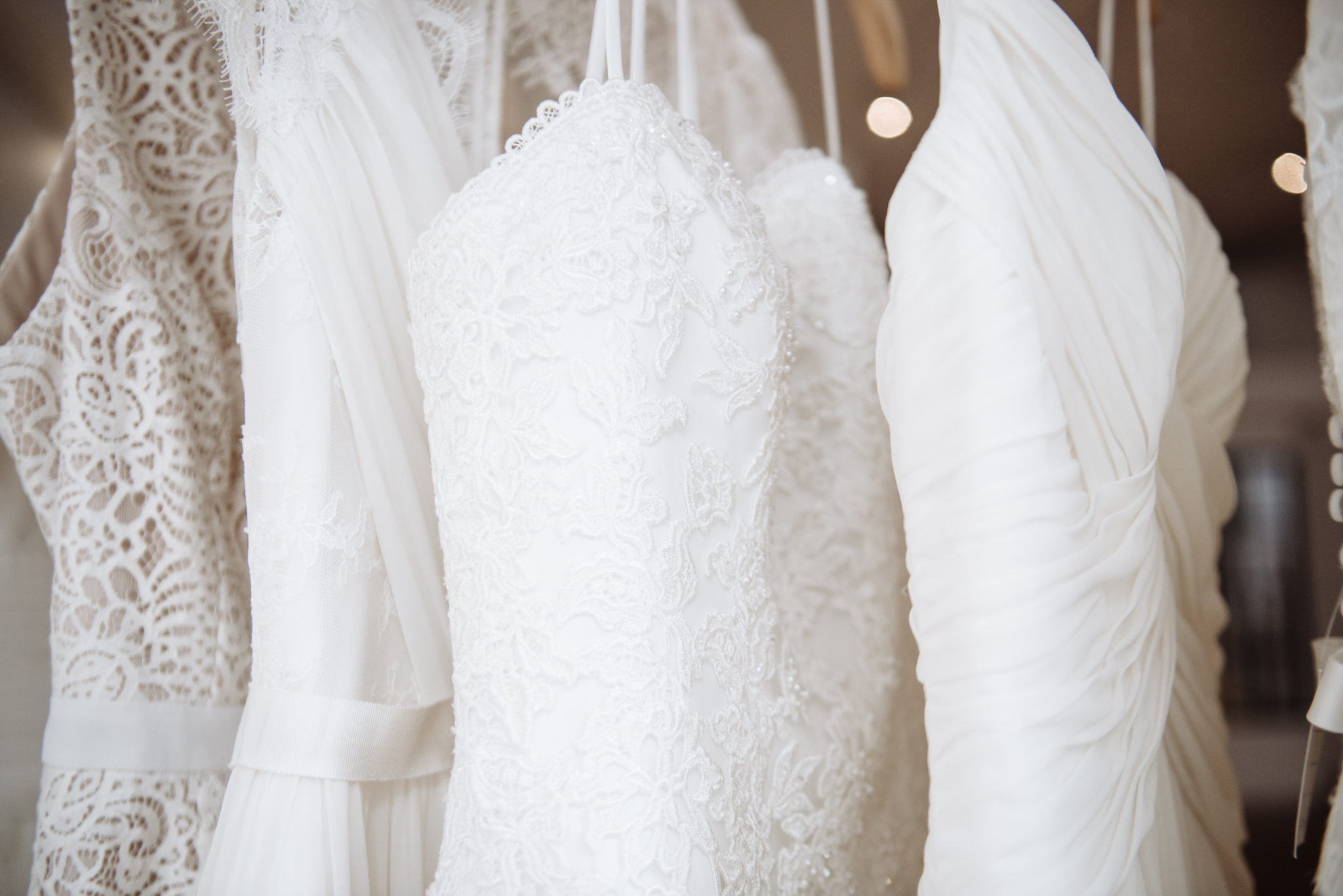 Four wedding dresses made from different fabrics hanging on a rack