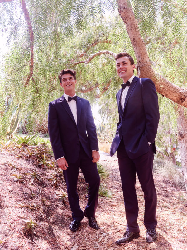 Two groomsmen in tuxedos in an outdoor setting