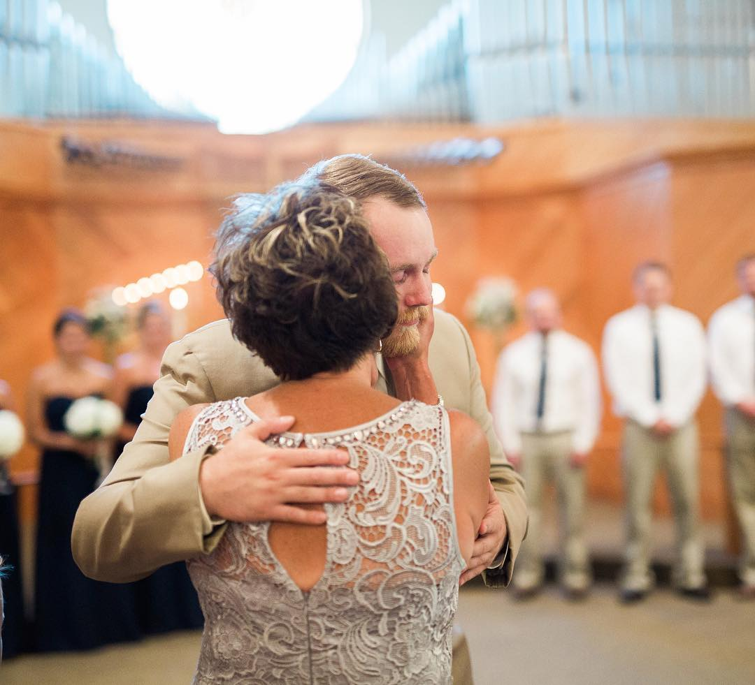 Mom kissing son on cheek at wedding