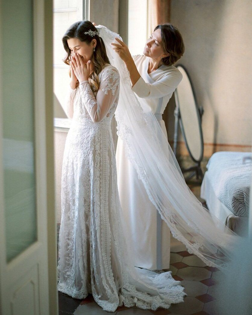 Bride smiling covering her face while mom clips in veil
