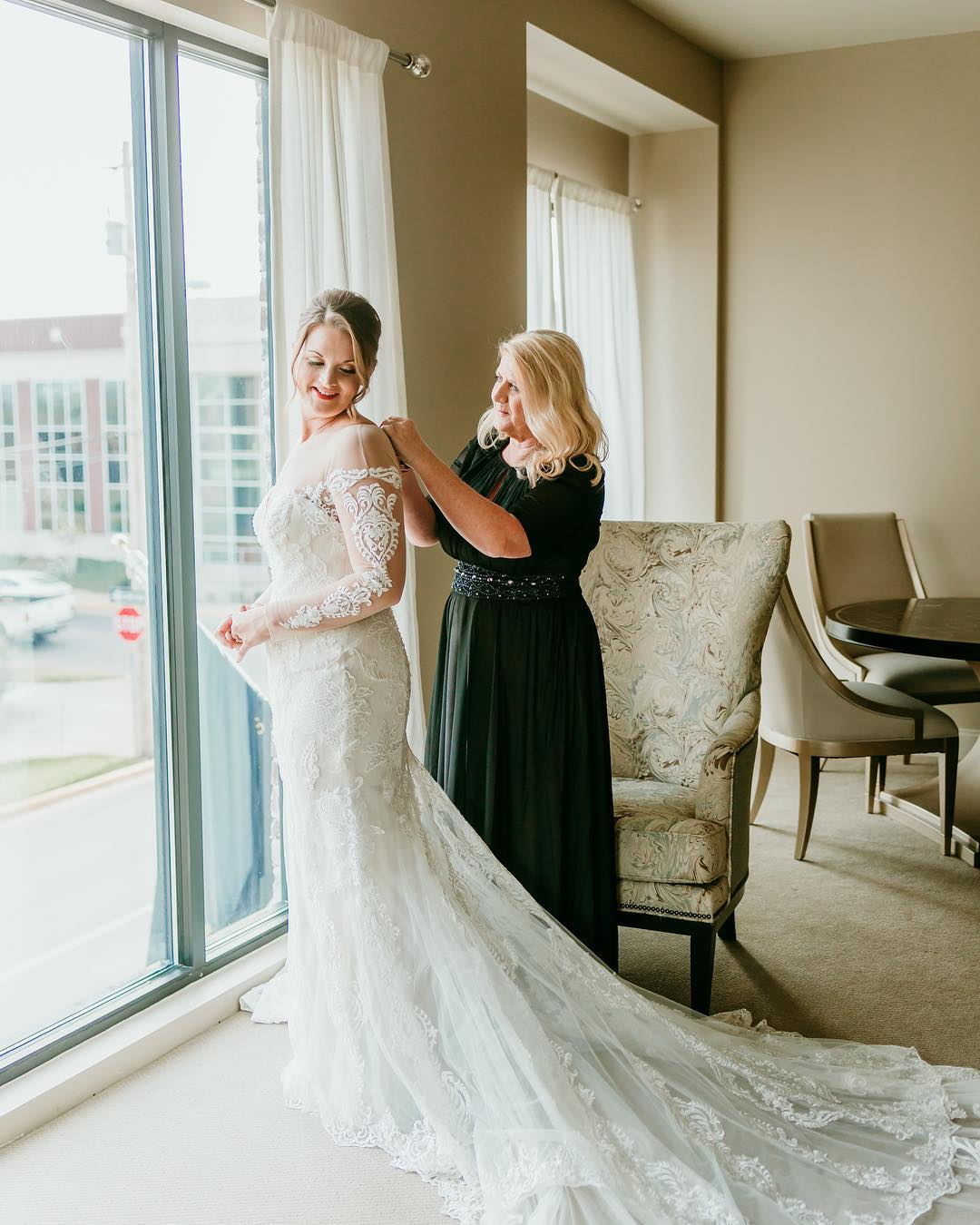 Bride in long sleeve wedding dress while mom secures zipper