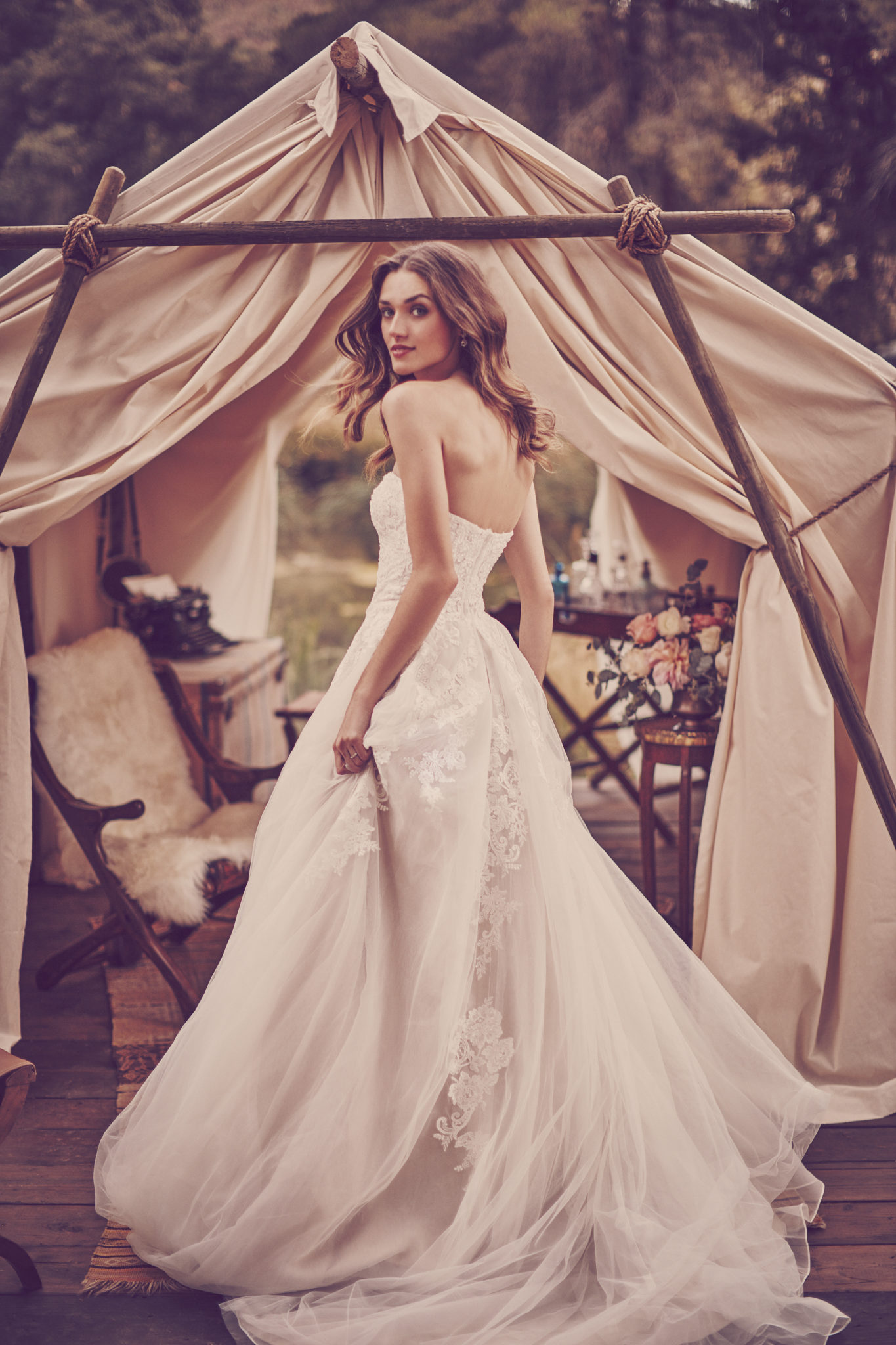 Bride in strapless ball gown wedding dress in front of rustic wedding tent
