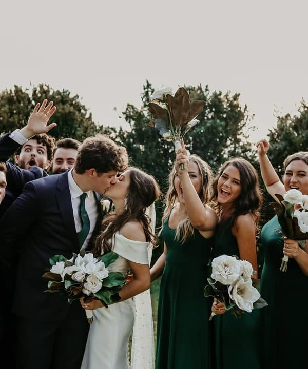Bride and Groom kissing with bridal party cheering in background
