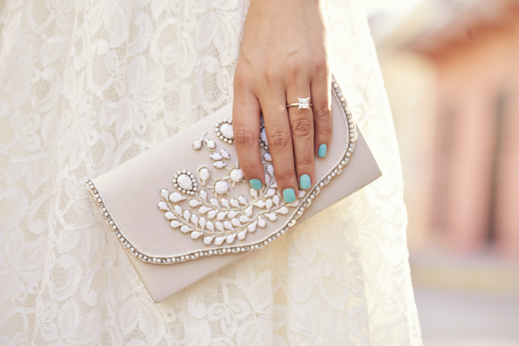 Hand with engagement ring holding beaded clutch