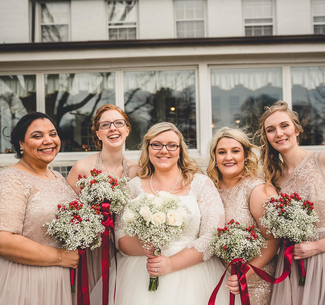 Gold bridesmaids with red bouquets