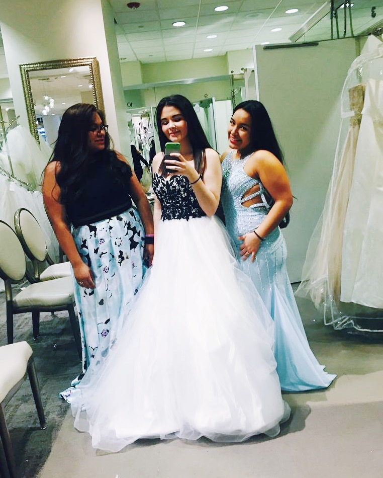 Mirror photo of three girls prom dress shopping