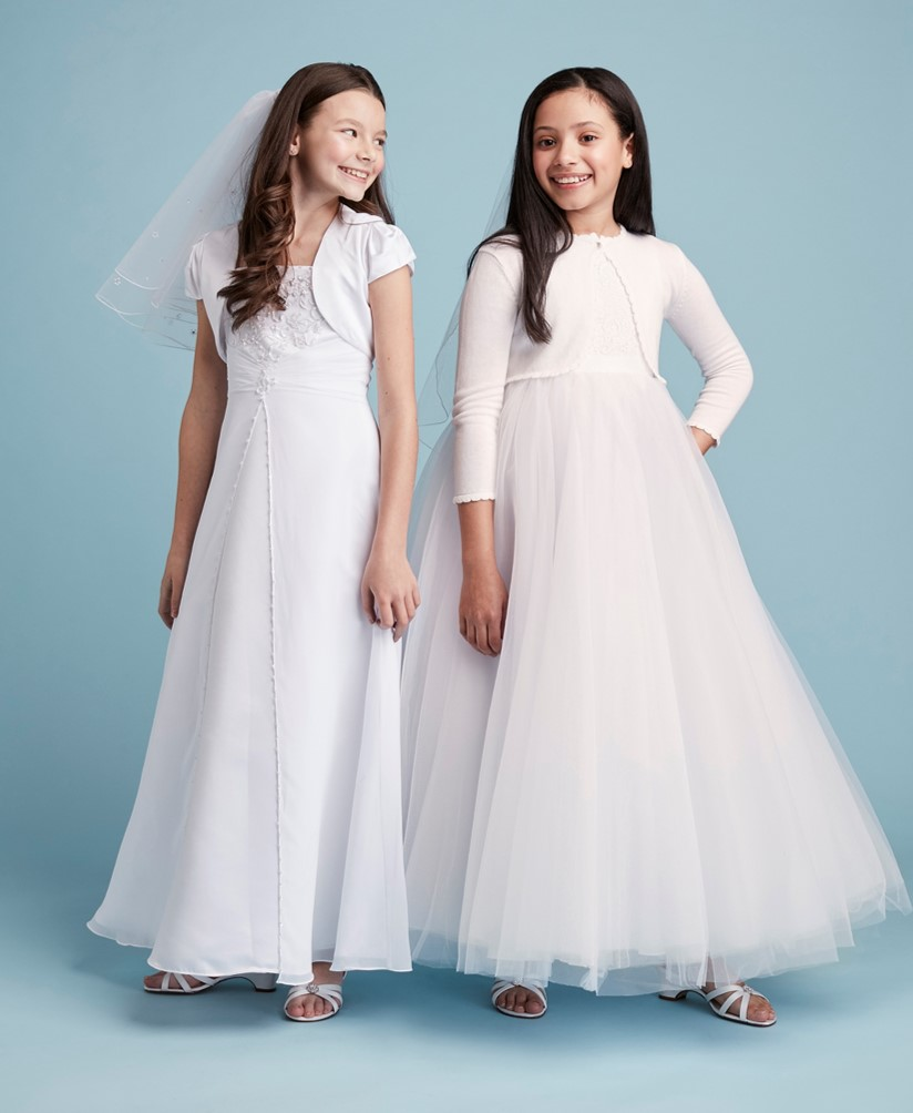 Two girls smiling in long white communion dresses