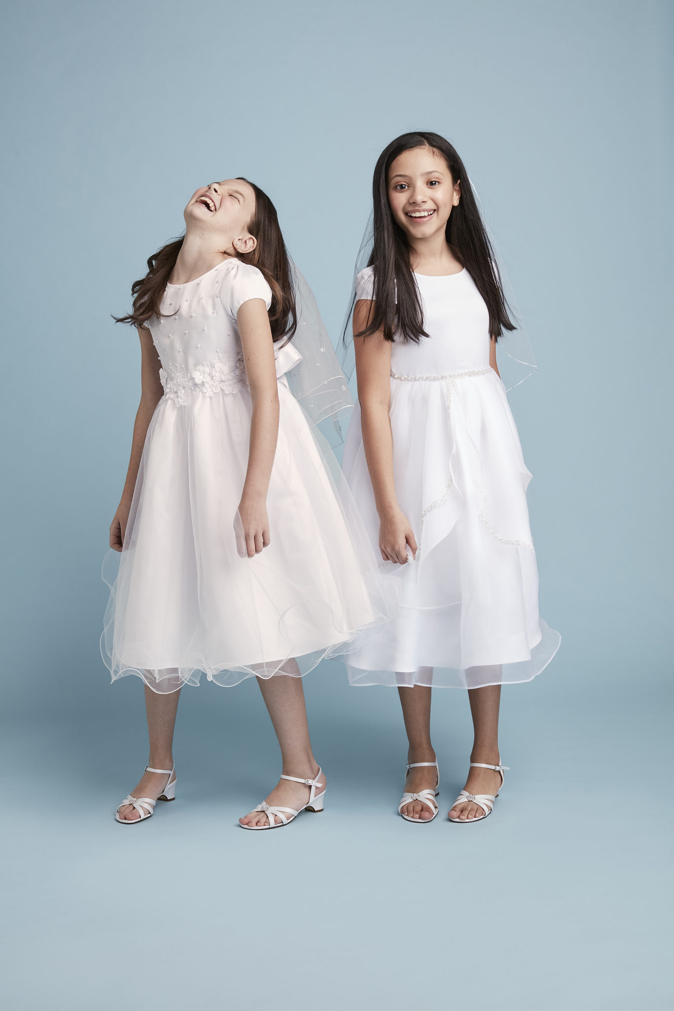 Two girls smiling in communion dresses from David's Bridal