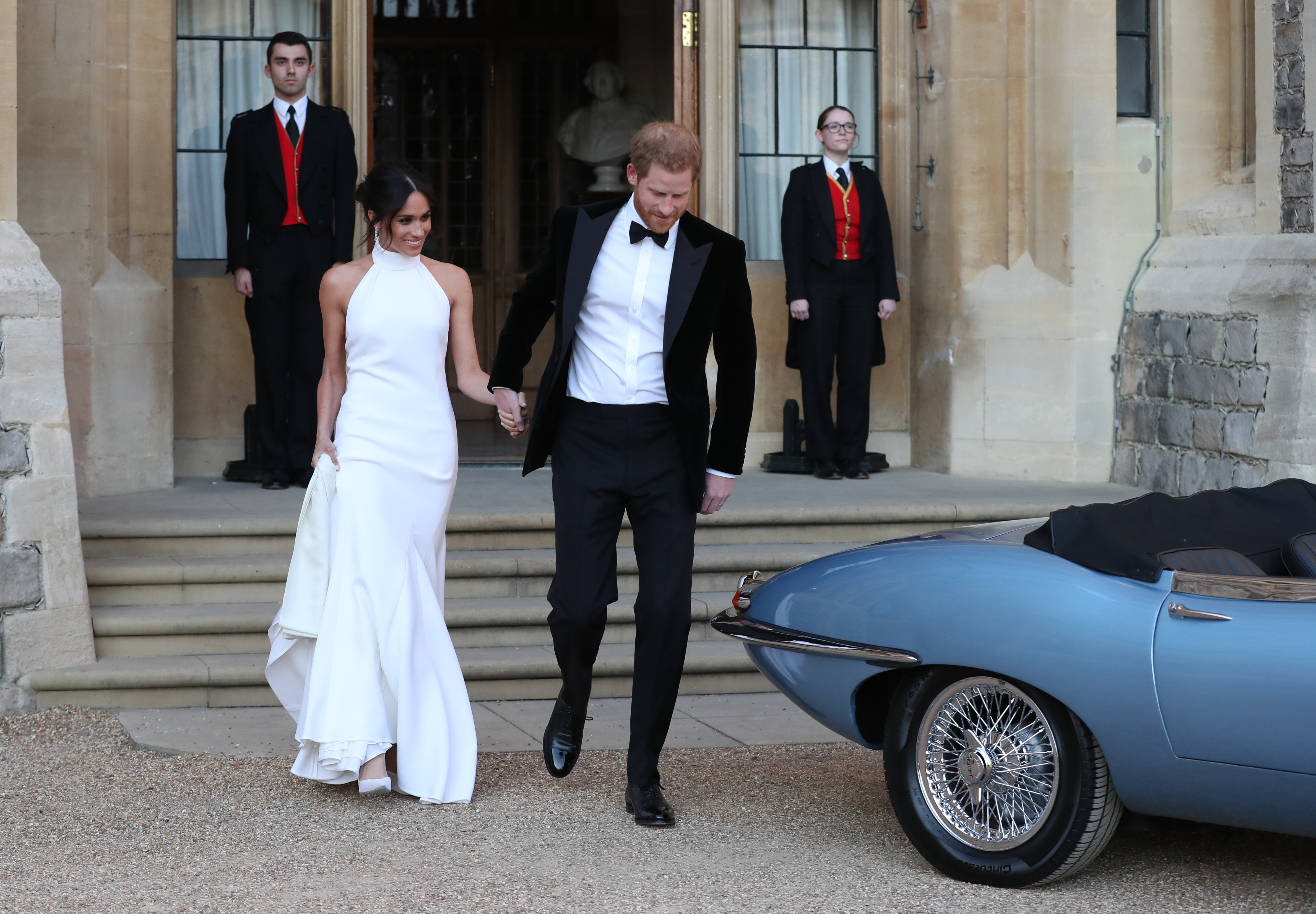 Meghan Markle and Prince Harry walking hand in hand to blue car to wedding reception