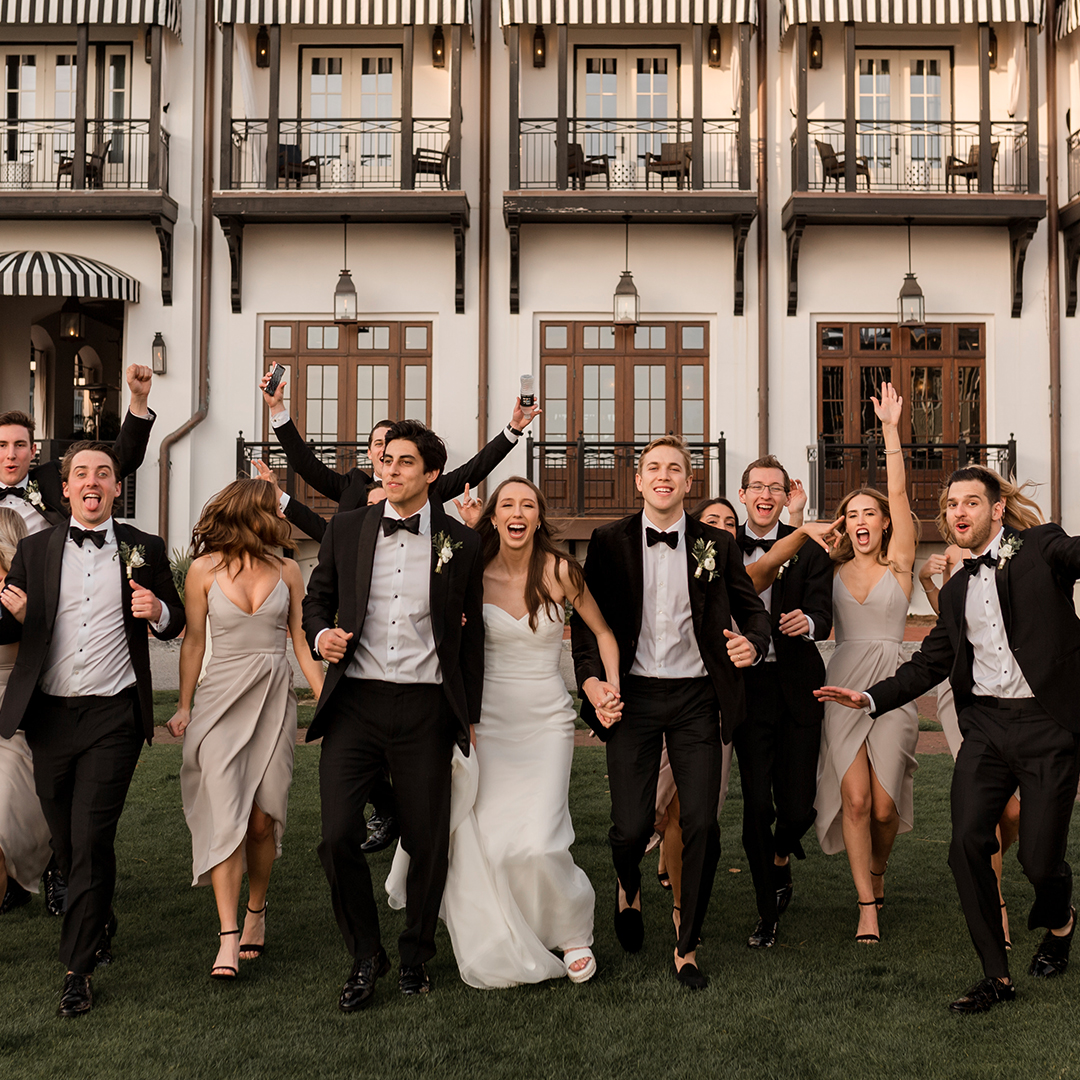 Bridal party holding hands and smiling, running on grass