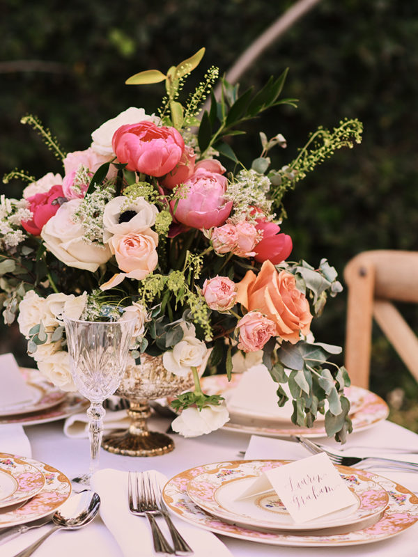 wedding table set up with flowers, fine china and place cards.