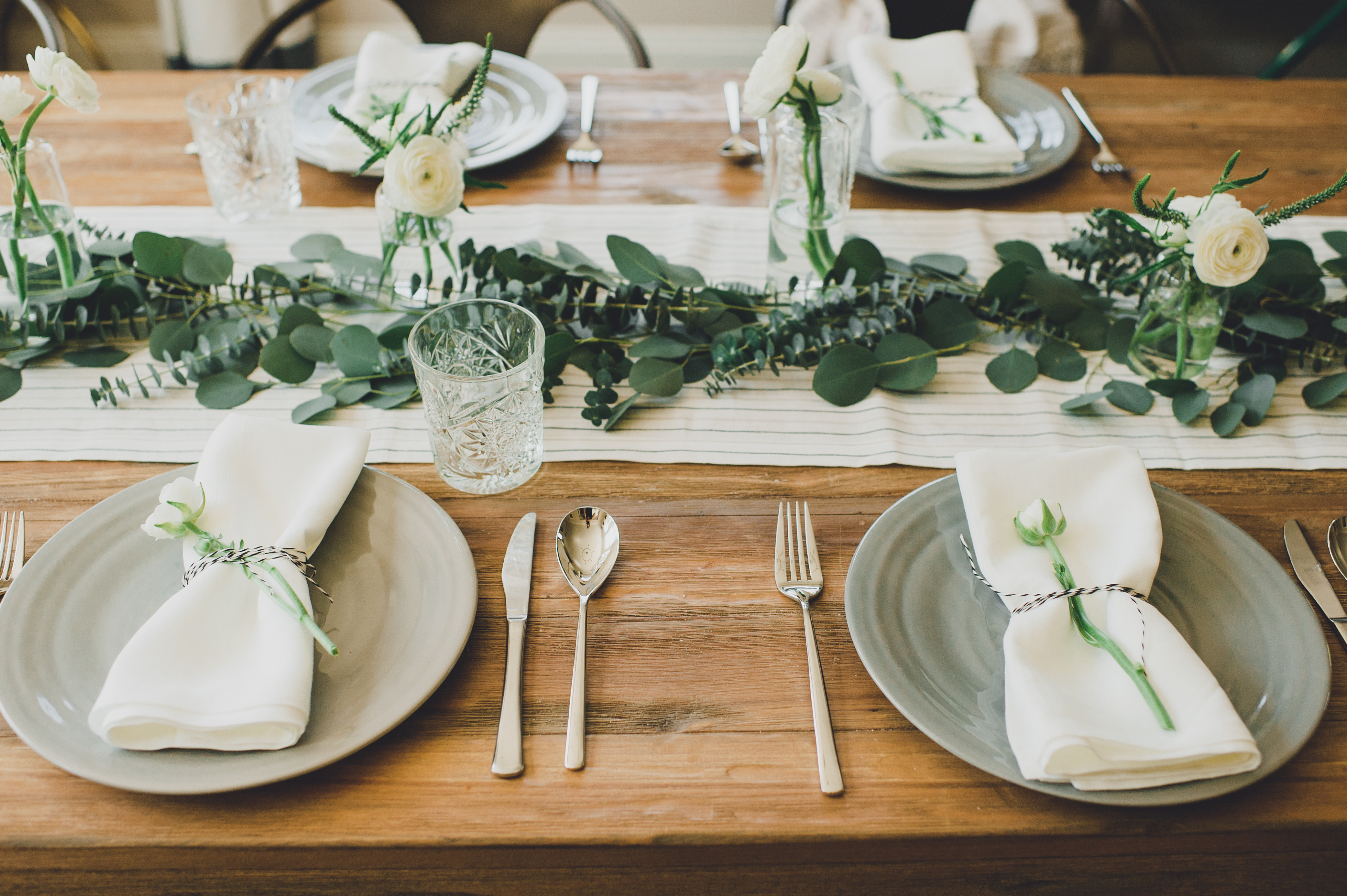 Dinner setting with dinner plates, glasses, flatware and flowers