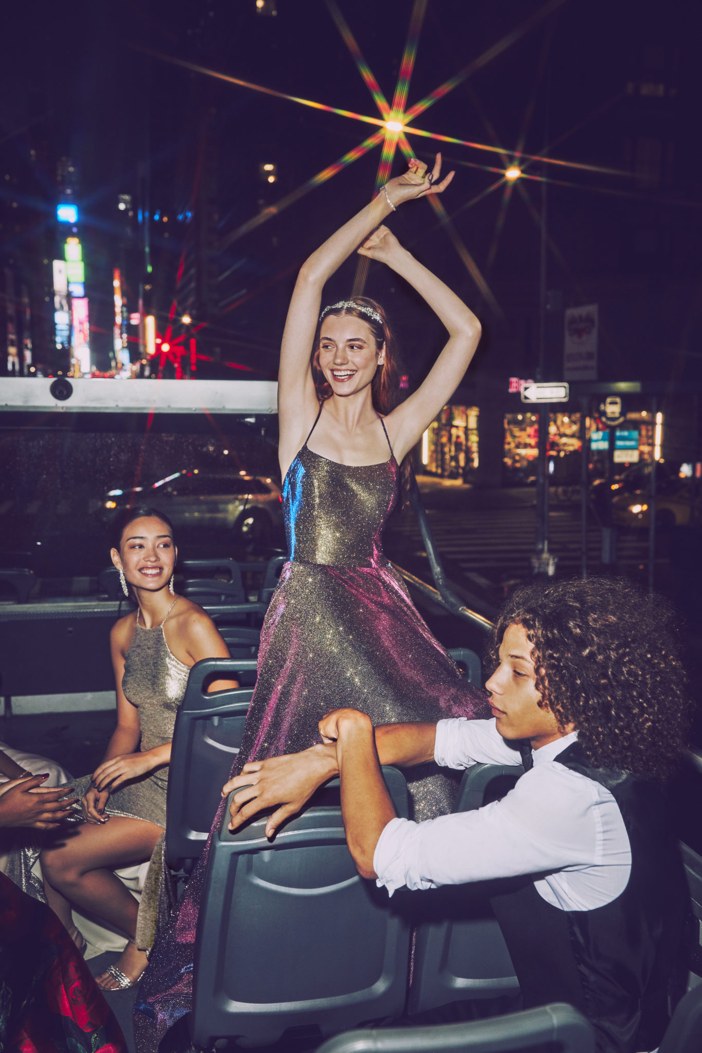 Girl in multicolored ball gown prom dress on bus in New York City