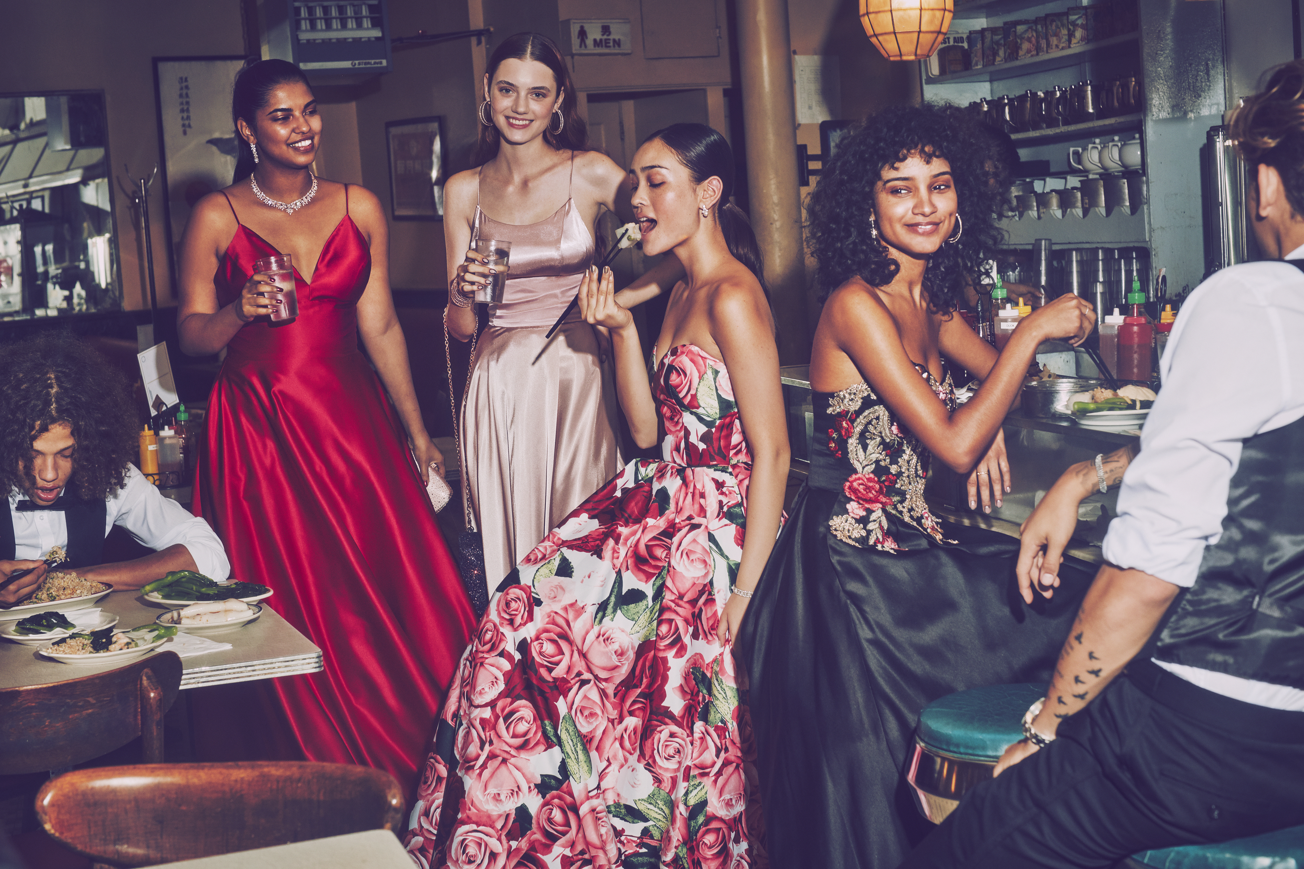 Girls in red, pink, floral print, and black prom dresses at a restaurant