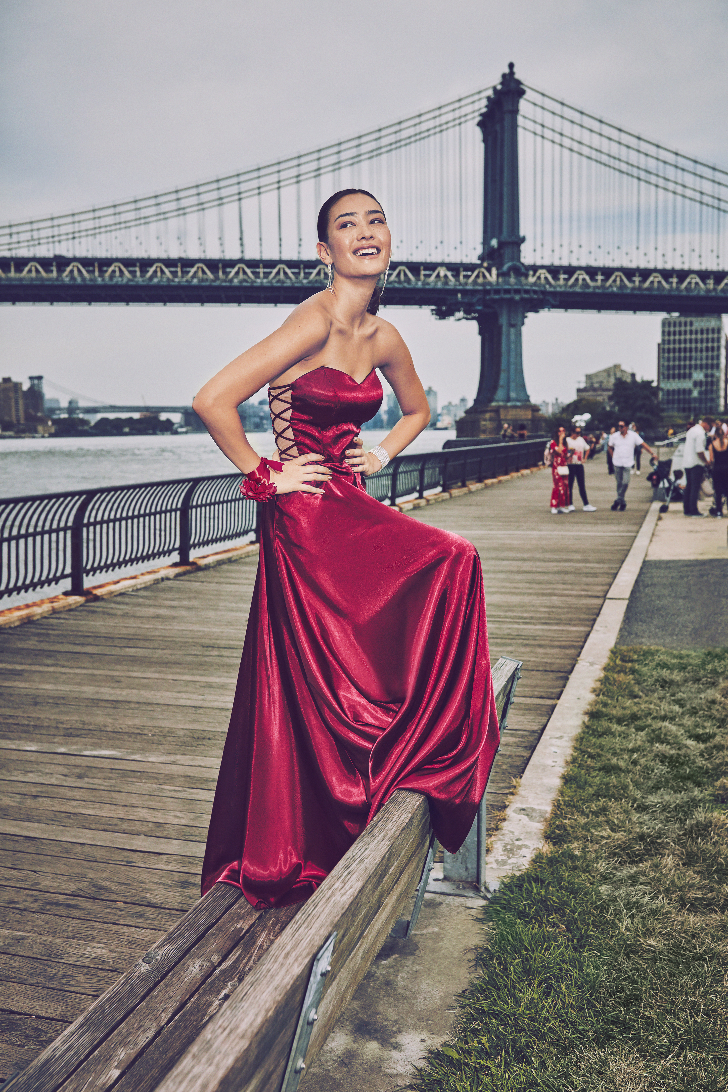 Girl in maroon strapless prom dress in front of the Brooklyn Bridge
