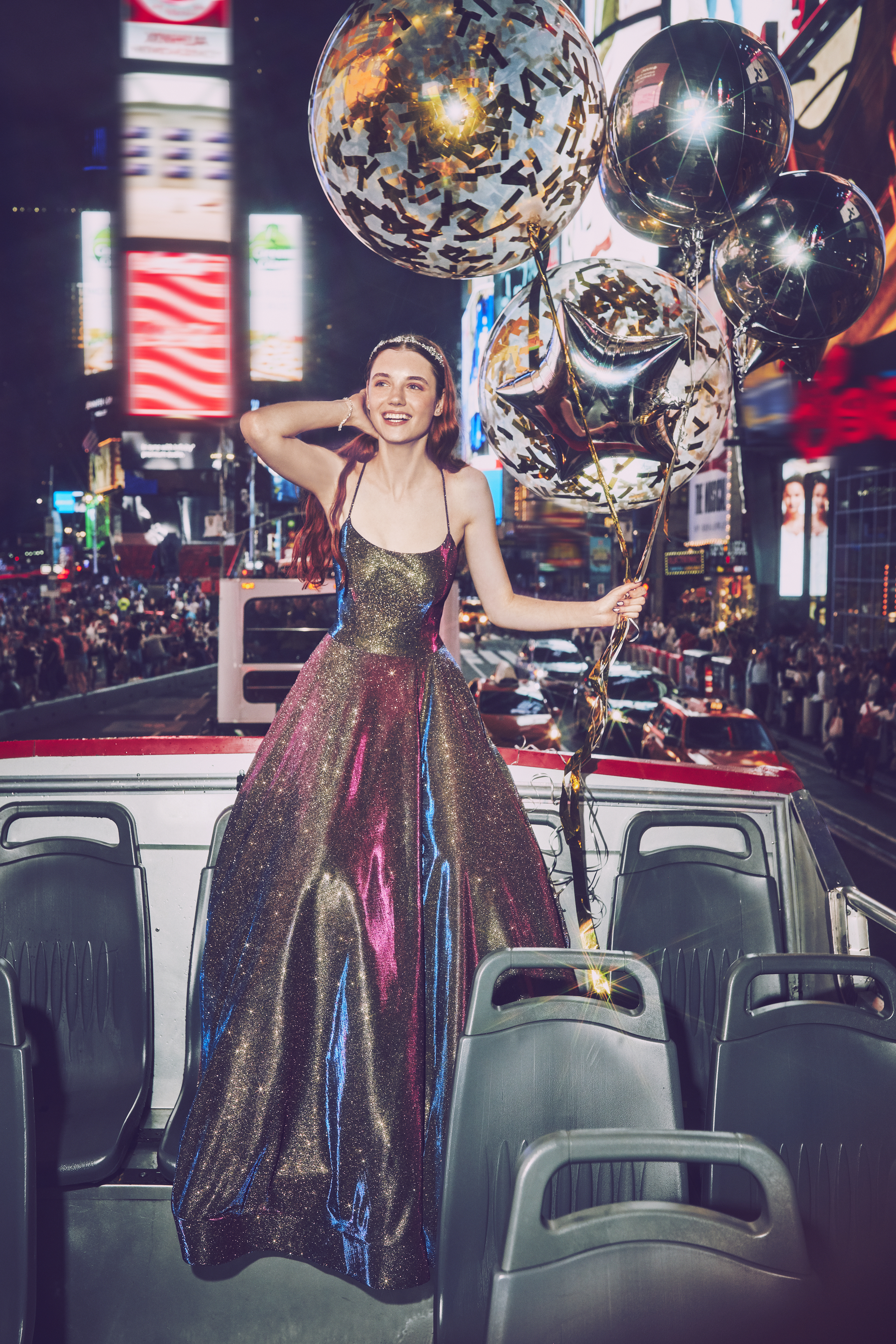 Girl in multicolored ball gown prom dress on a bus in Times Square New York holding balloons