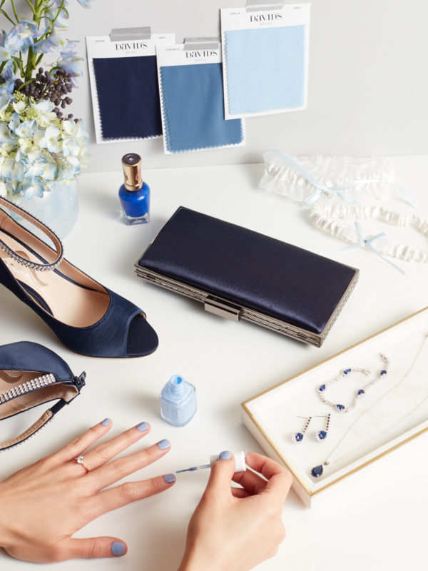 Hand being painted with light blue nail polish with blue heels, handbag, and jewelry on table.