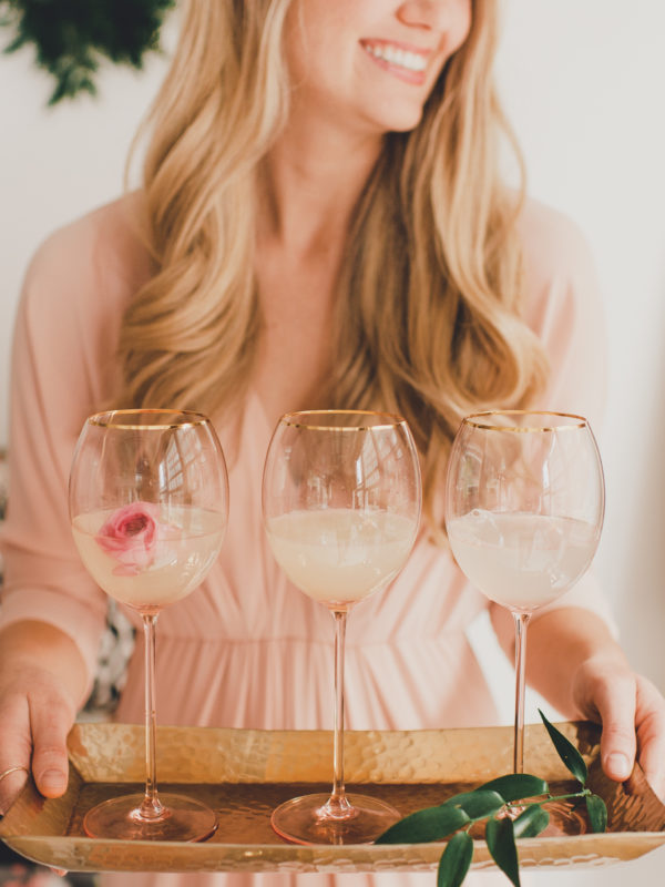 Blonde Woman holding tray of rose wine glasses.