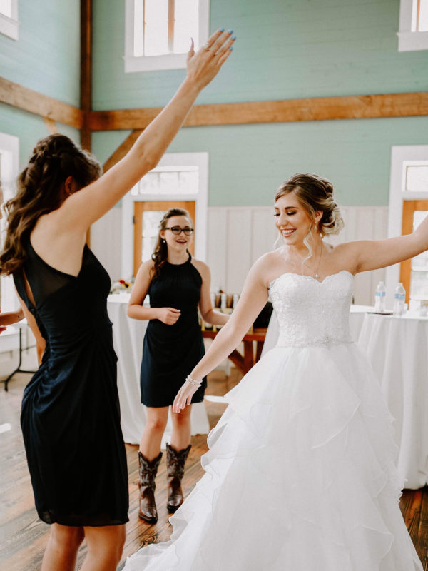 Bride in white dress with dancing with her bridesmaids