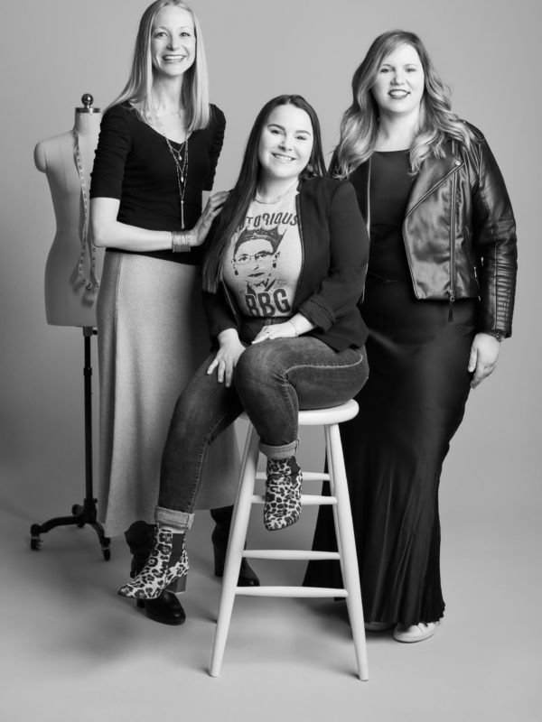 Three women from David's Bridal's merchandising team in a photo studio setting
