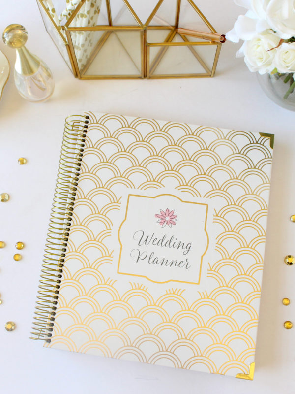 White and gold wedding planning notebook on a white table with a white and gold tea cup and vase of white roses
