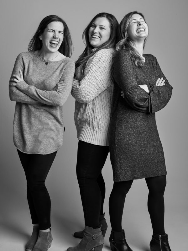 Three women from David's Bridal's PR & Social Media laughing in a photo studio setting