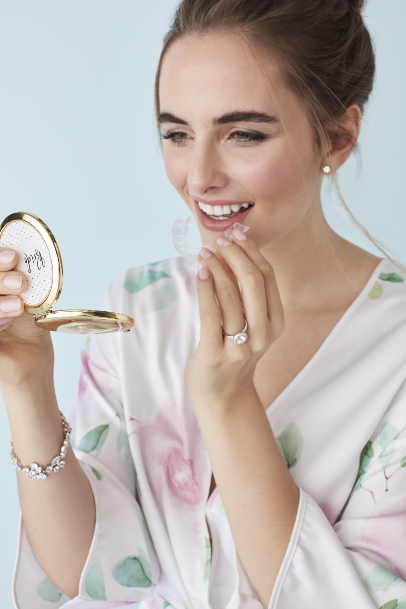bride with teeth aligning tray and compact mirror