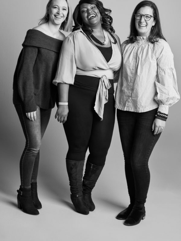 Three women from David's Bridal's Digital team smiling and pictured in a photo studio setting)