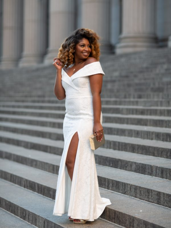 African American woman in a long white off-the-shoulder dress and gold accessories standing on marble steps outside a grand building