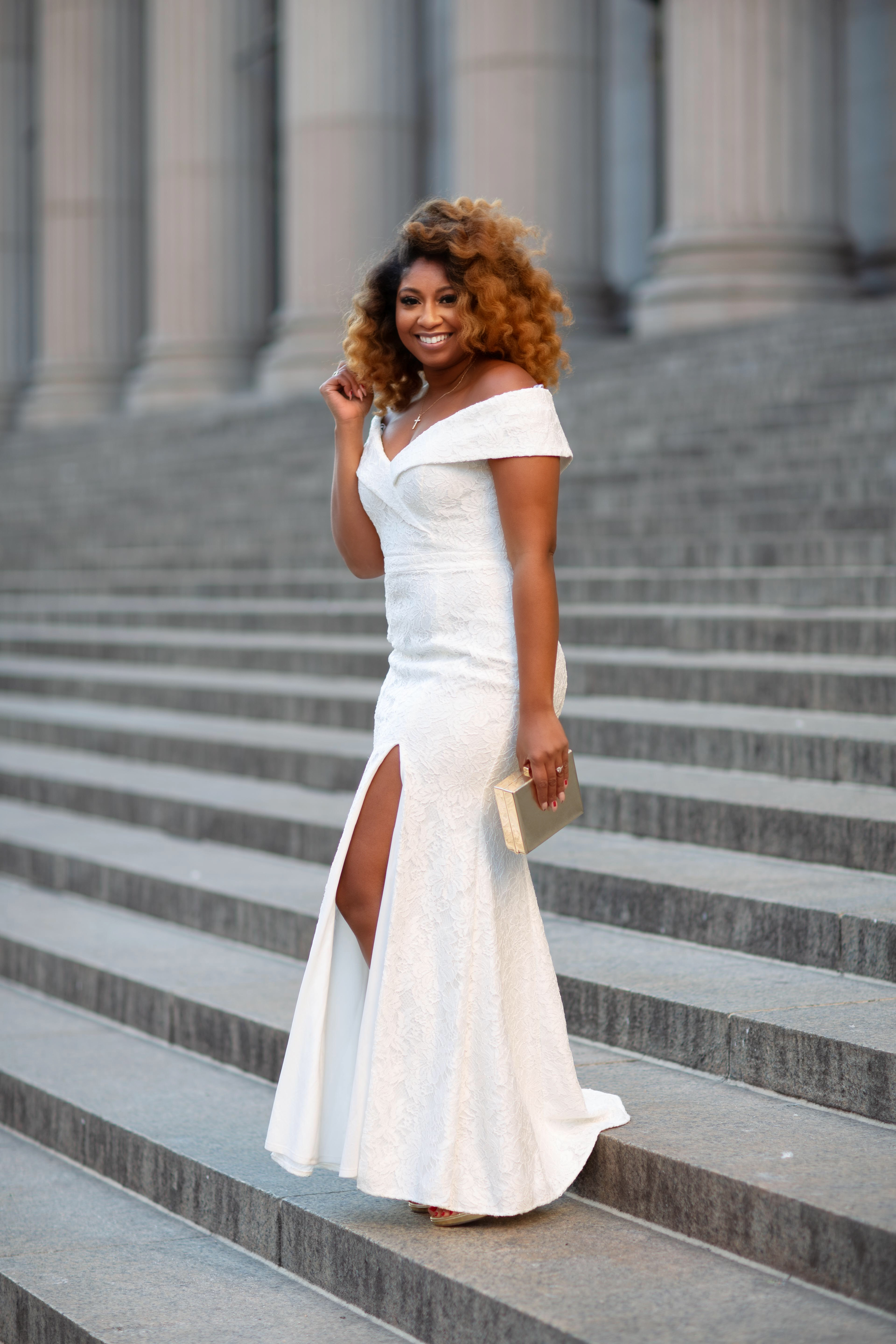 African American woman standing on marble stairs in a long white off-the-shoulder dress and gold accessories