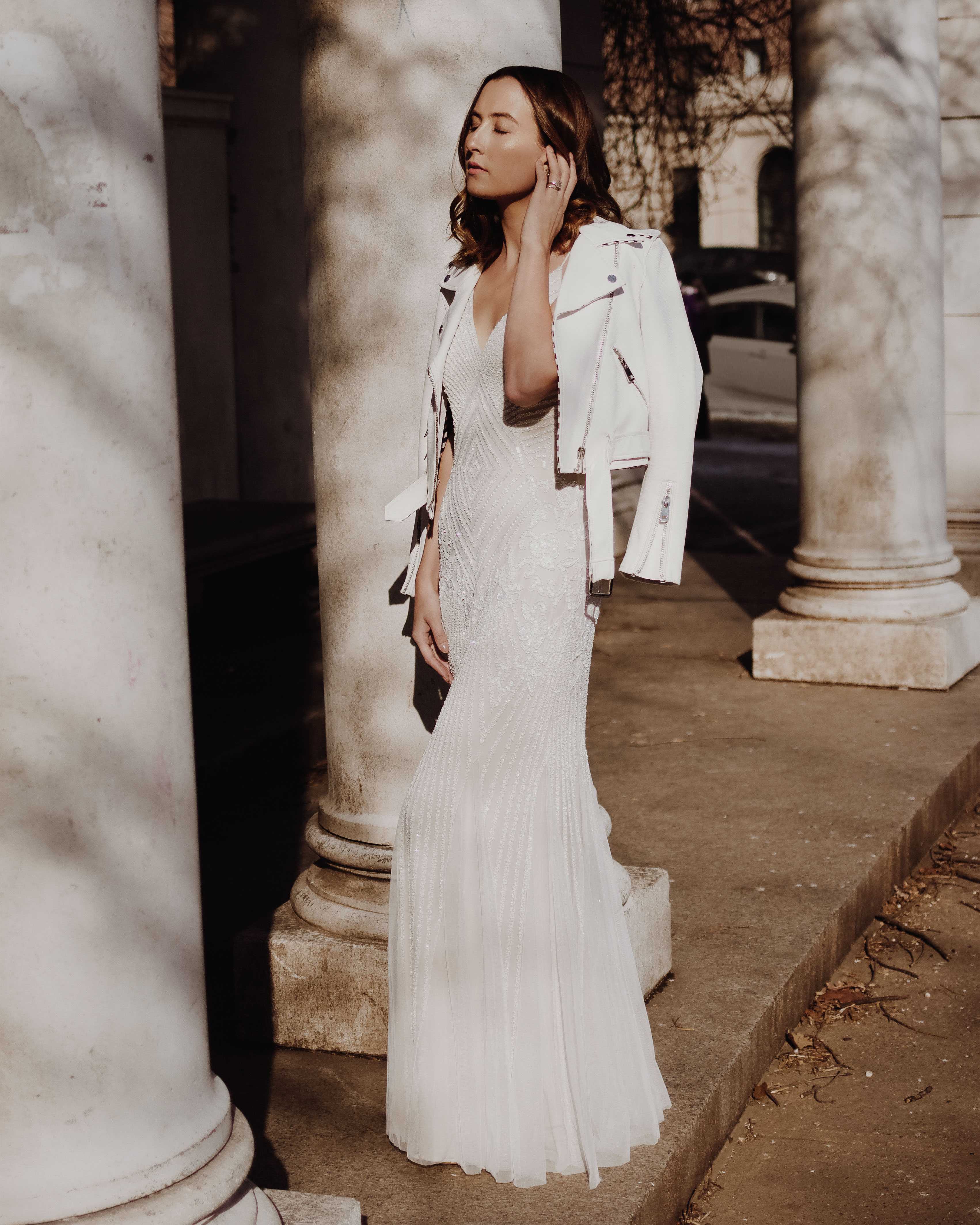 Woman standing near white pillars in a long white beaded dress with white leather jacket draped over her shoulders
