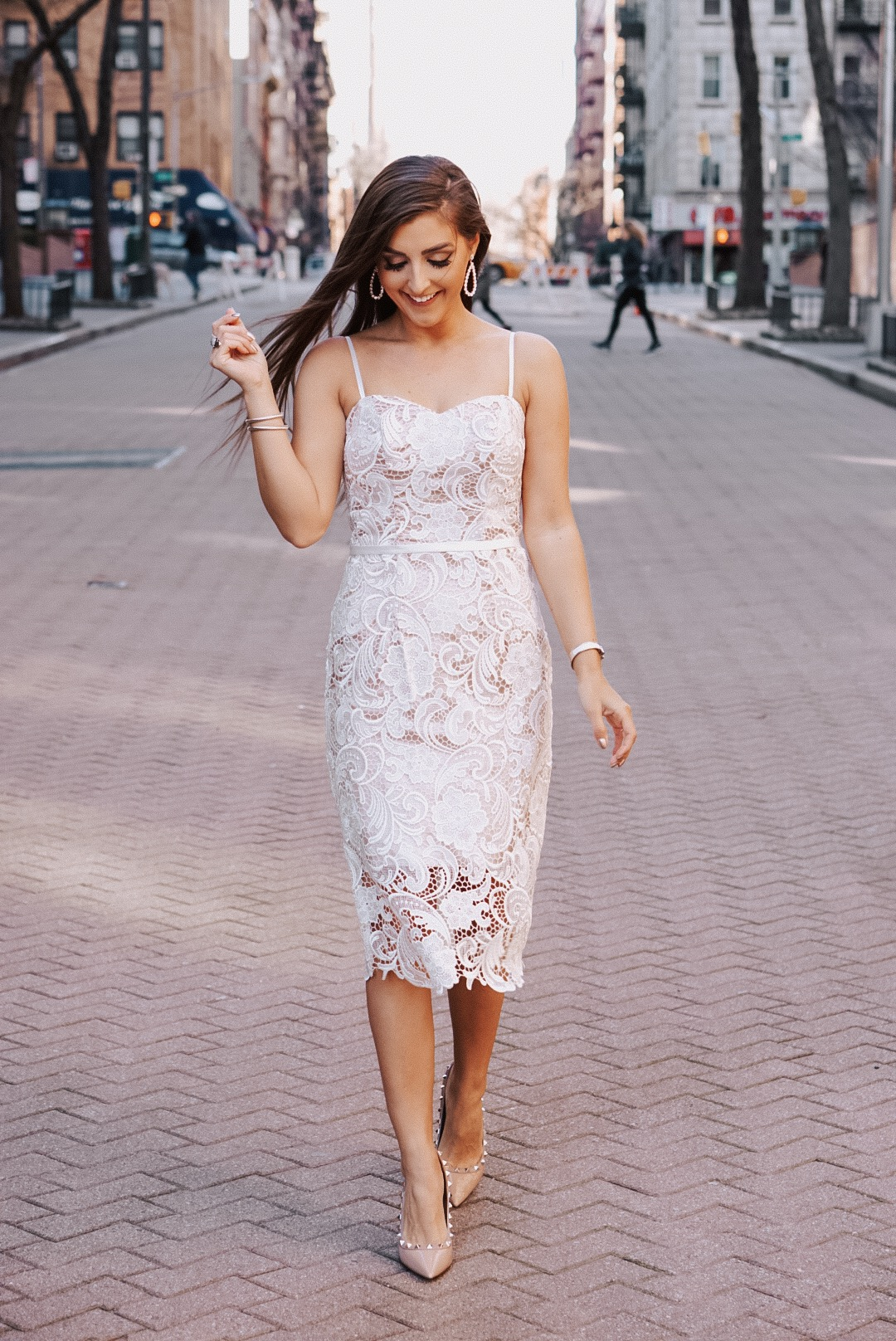 Woman in a short spaghetti strap lace dress standing on a brick road