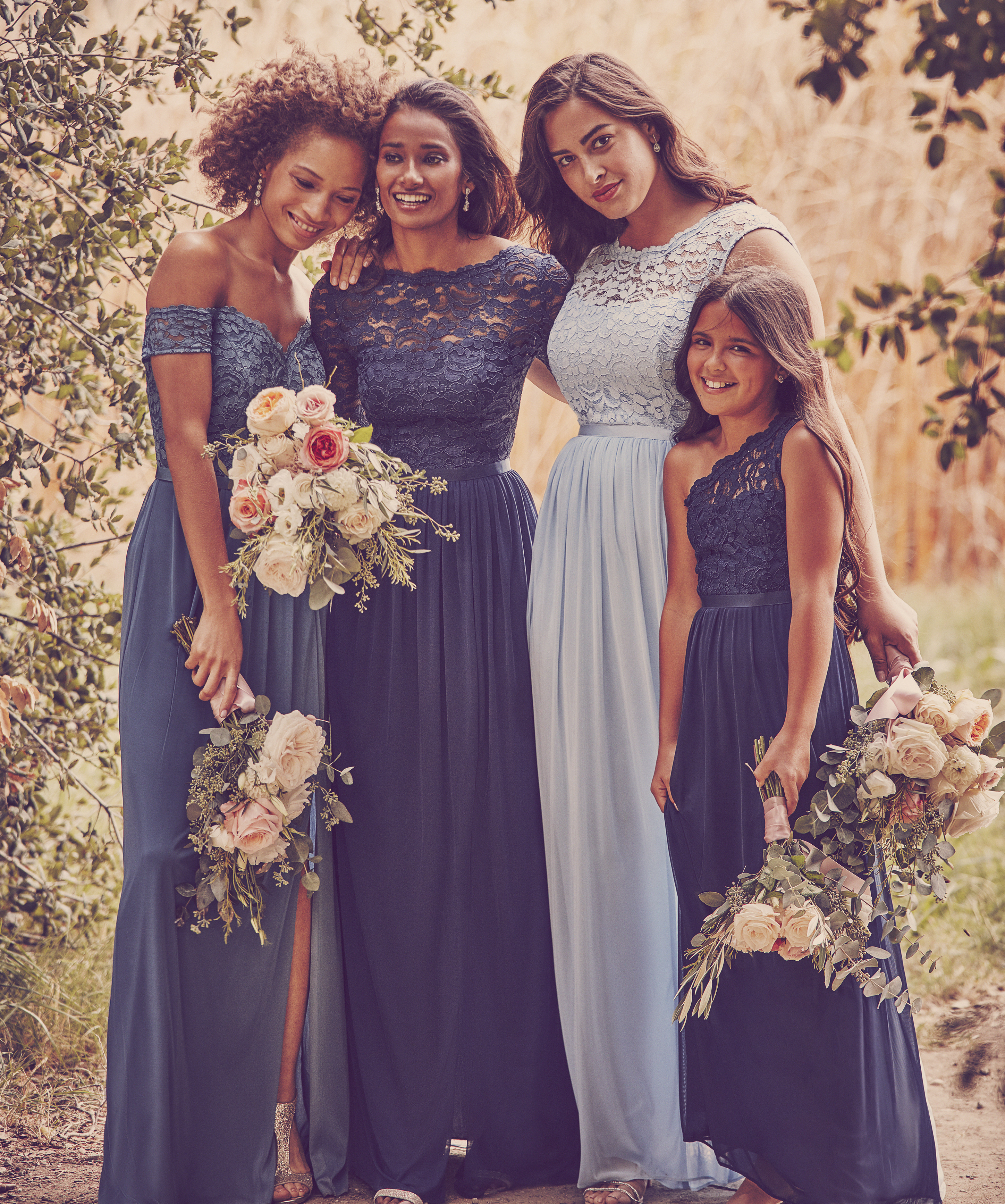 Women and child smiling in long lace bridesmaid dresses