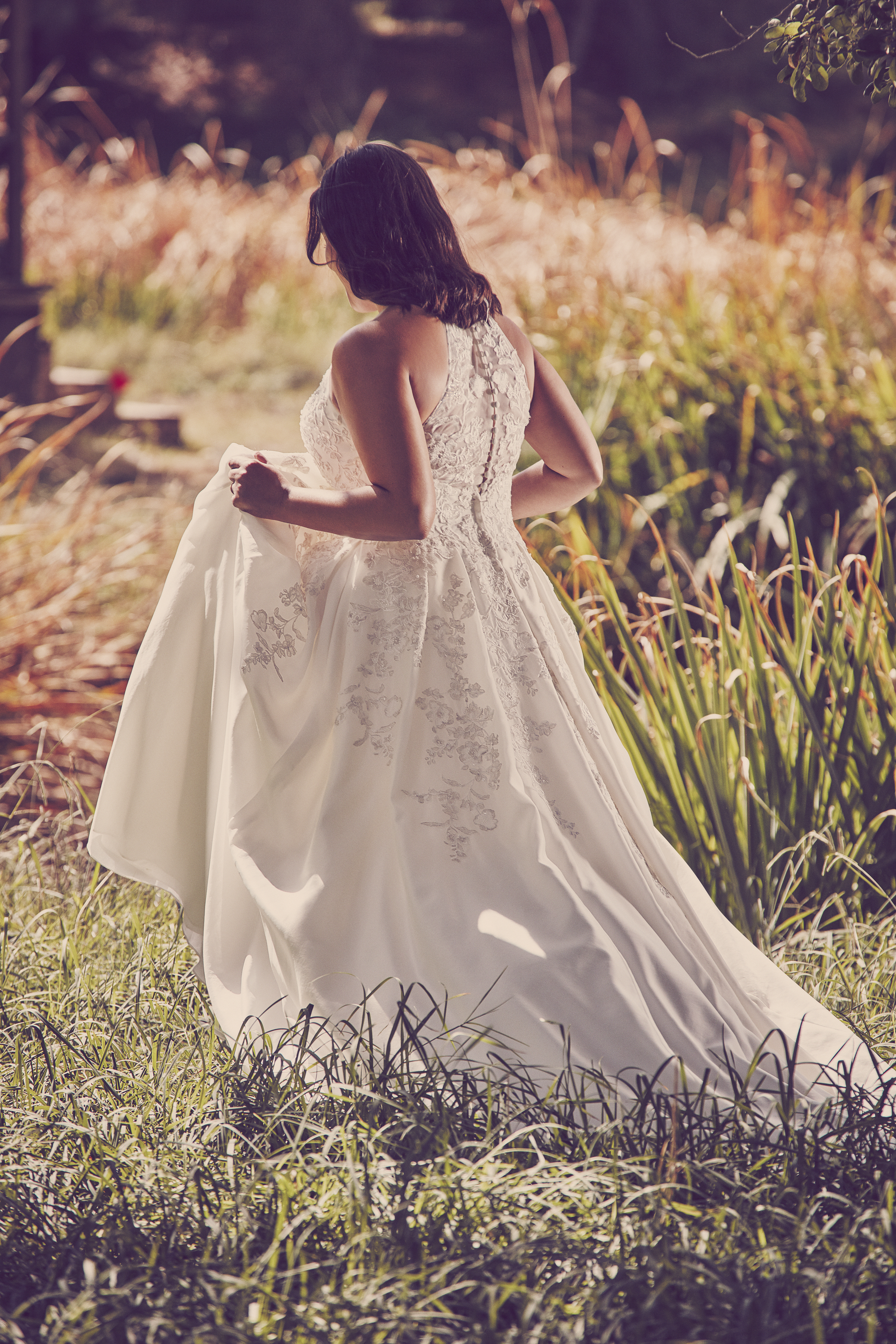 Woman walking in grass holding up skirt of ball gown wedding dress