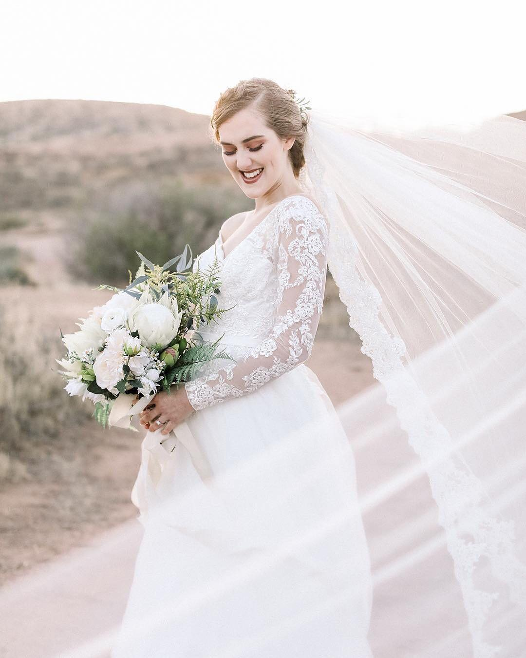 Bride wearing a lace trim cathedral length veil     Insta-Worthy Veils