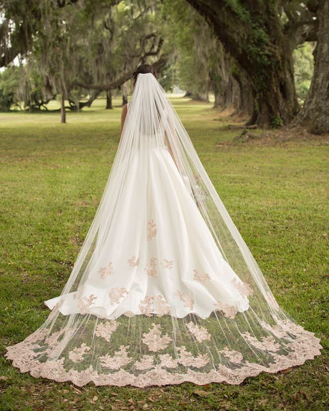 Bride in a rose gold lace cathedral veil on grass     Insta-Worthy Veils