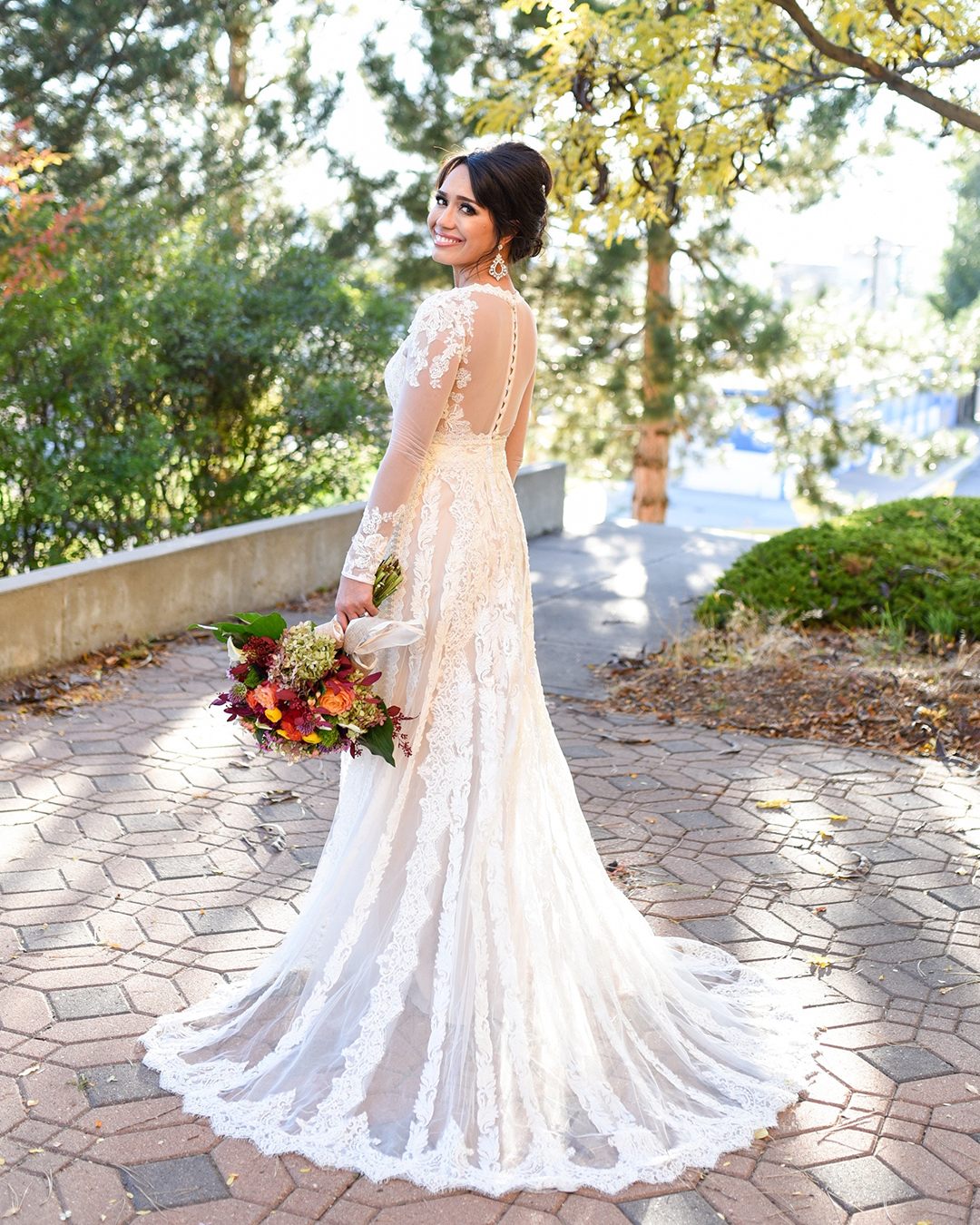 Bride in a long-sleeve lace gown showing off the back details of her dress in a garden setting.