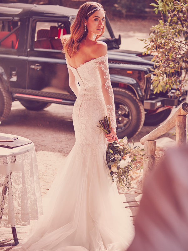 Bride from behind in a long sleeve off-the-shoulder trumpet wedding dress with lace details