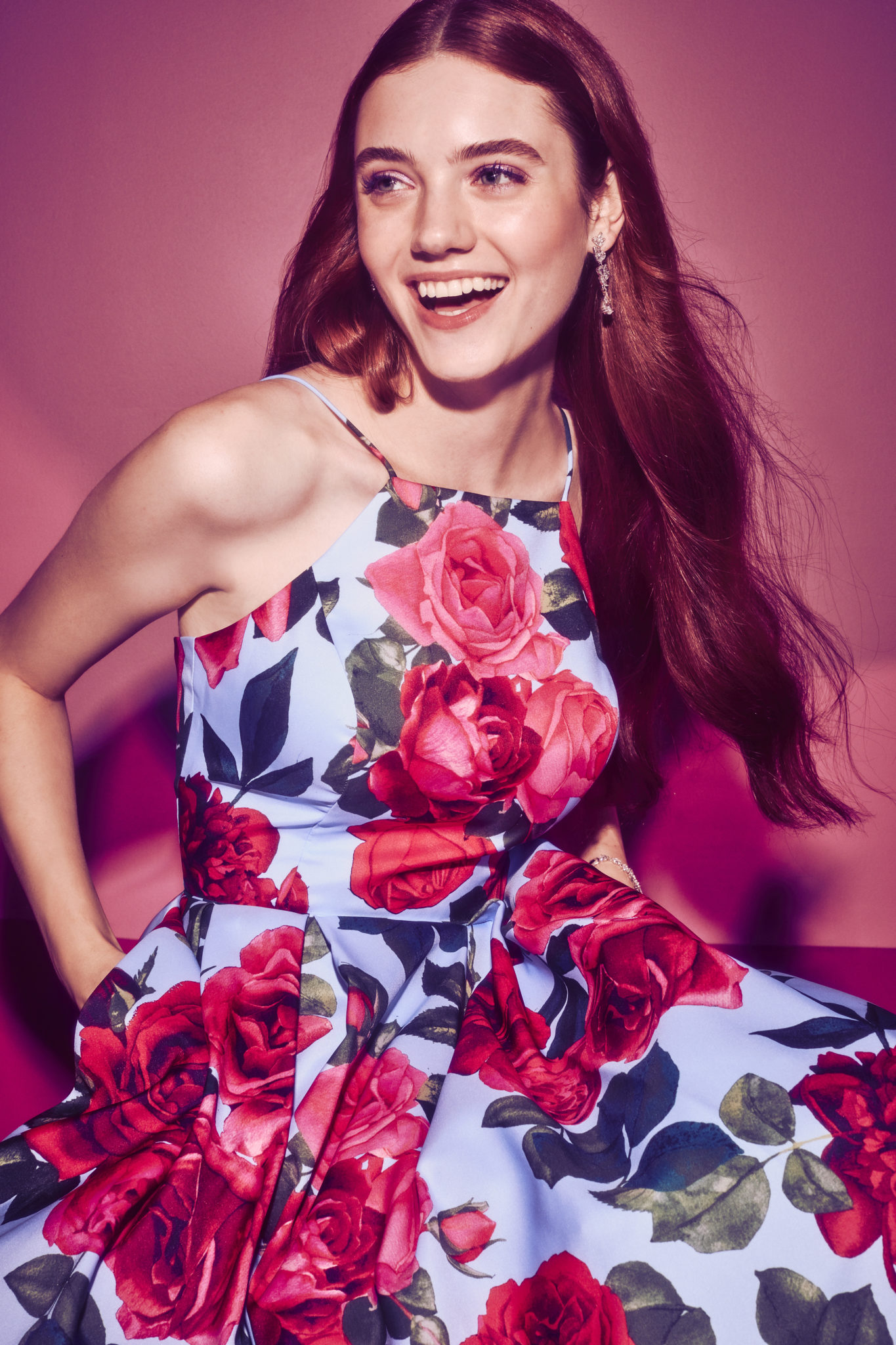 Smiling girl in floral print prom dress with hands in pockets