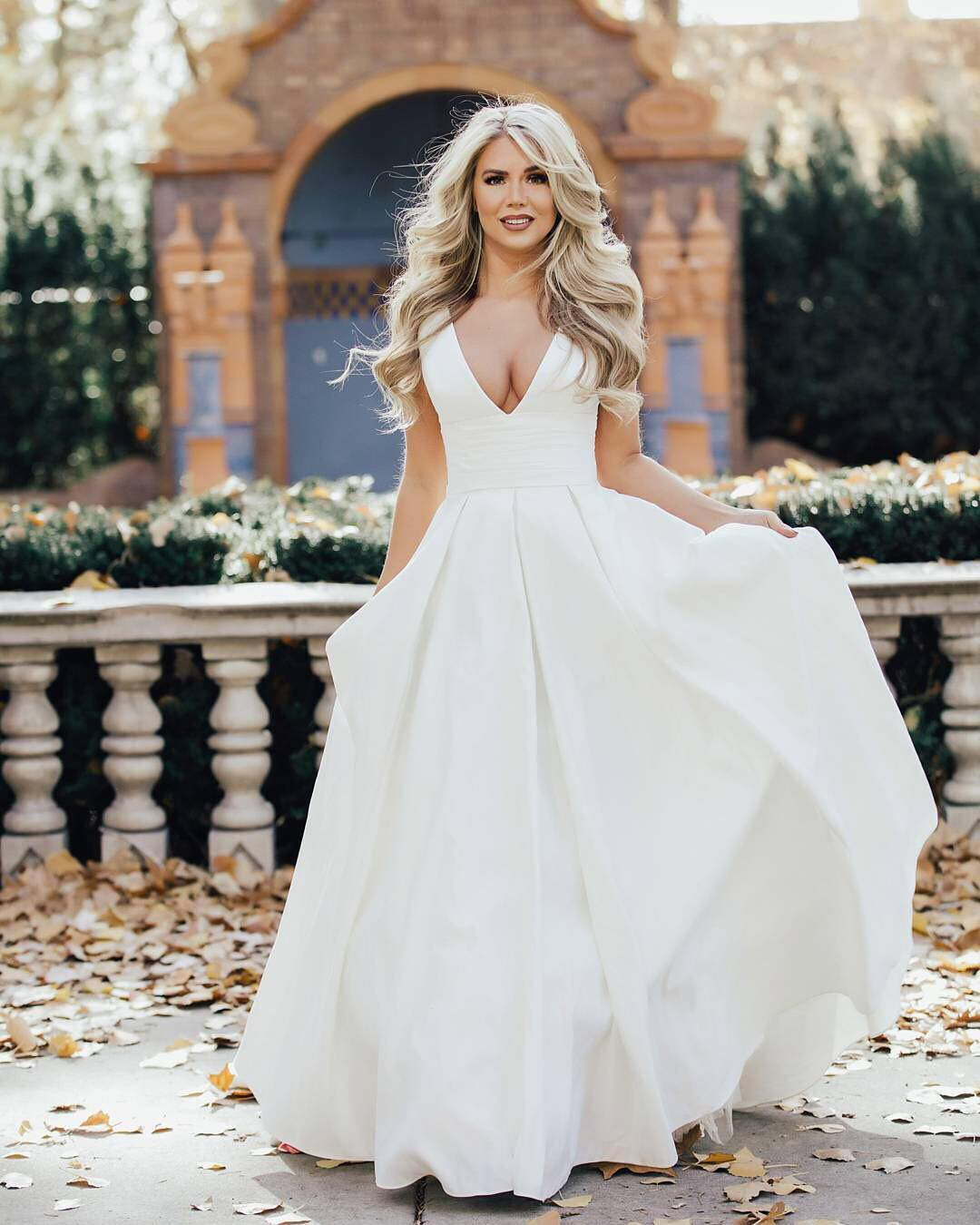 Bride in a plunging V-neck ball gown in a garden setting.