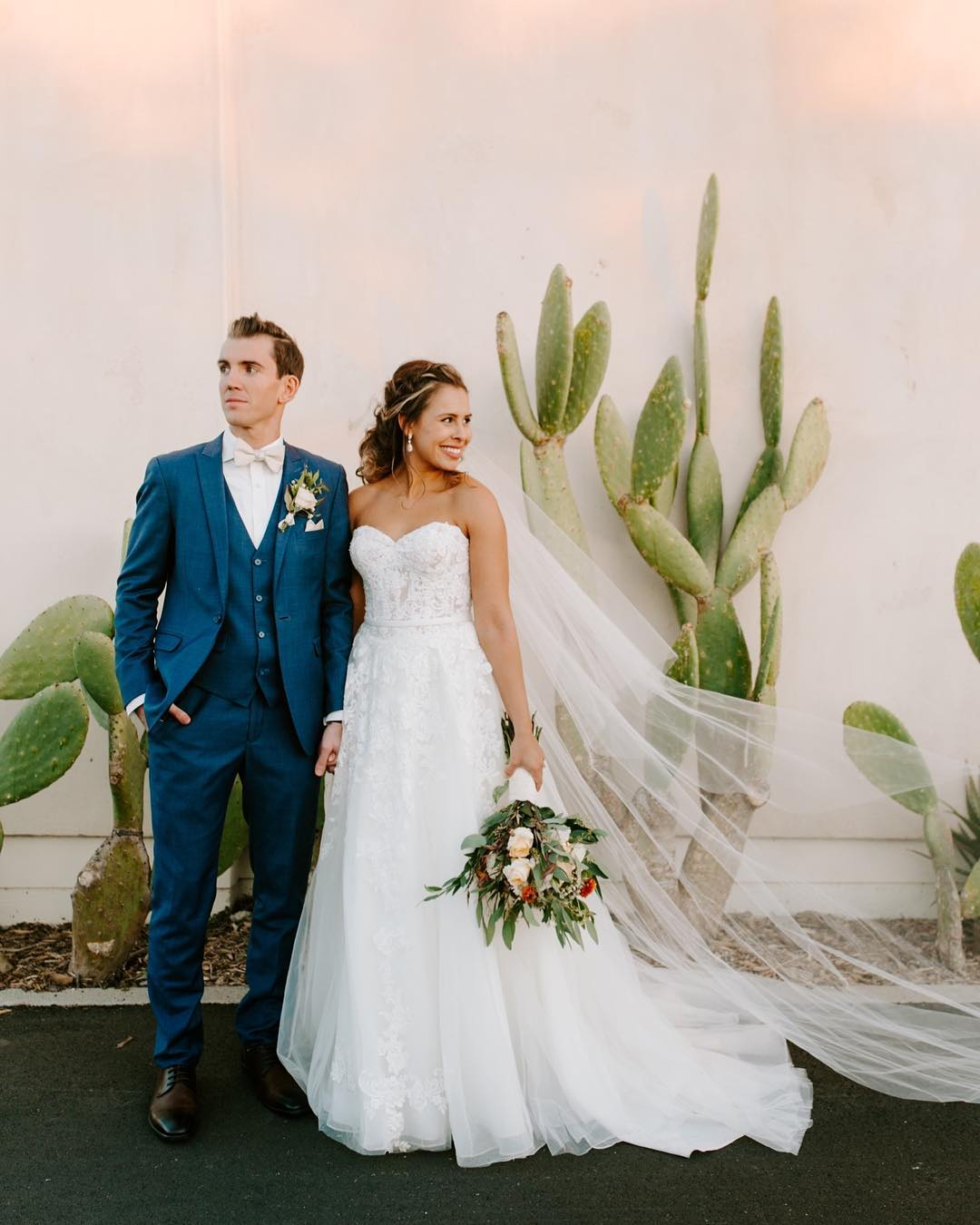Bride in strapless ballgown with groom in blue three-piece suit stand near a cactus.