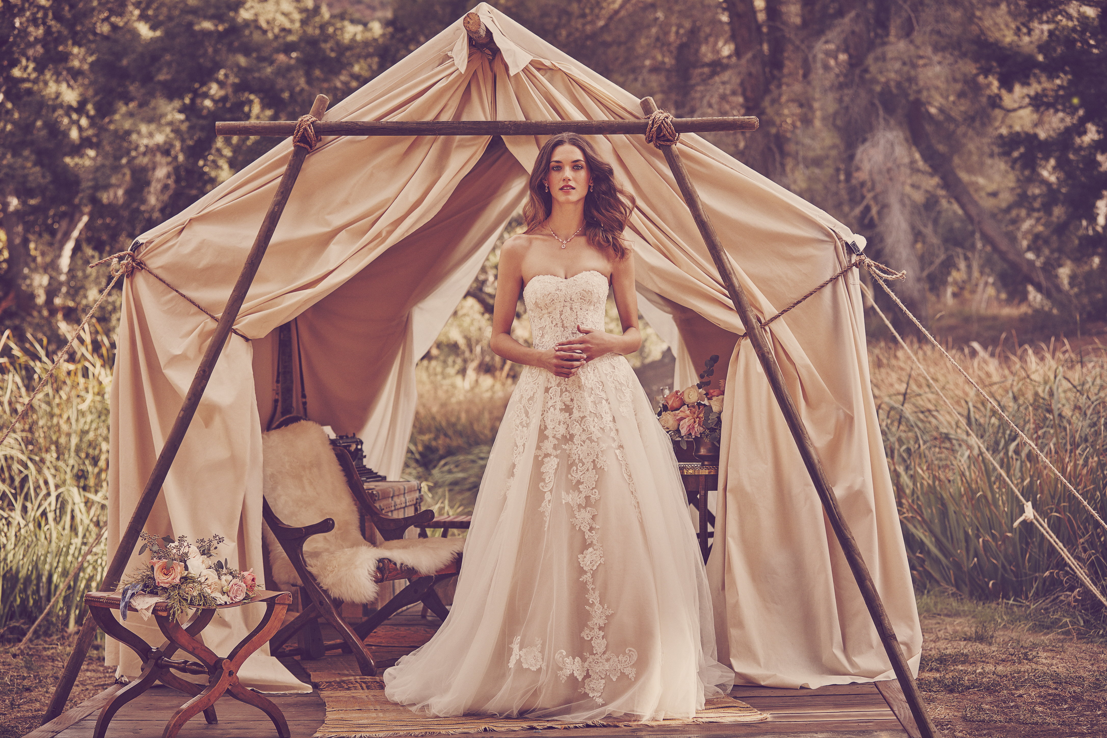 Woman standing in front of tent in ball gown wedding dress