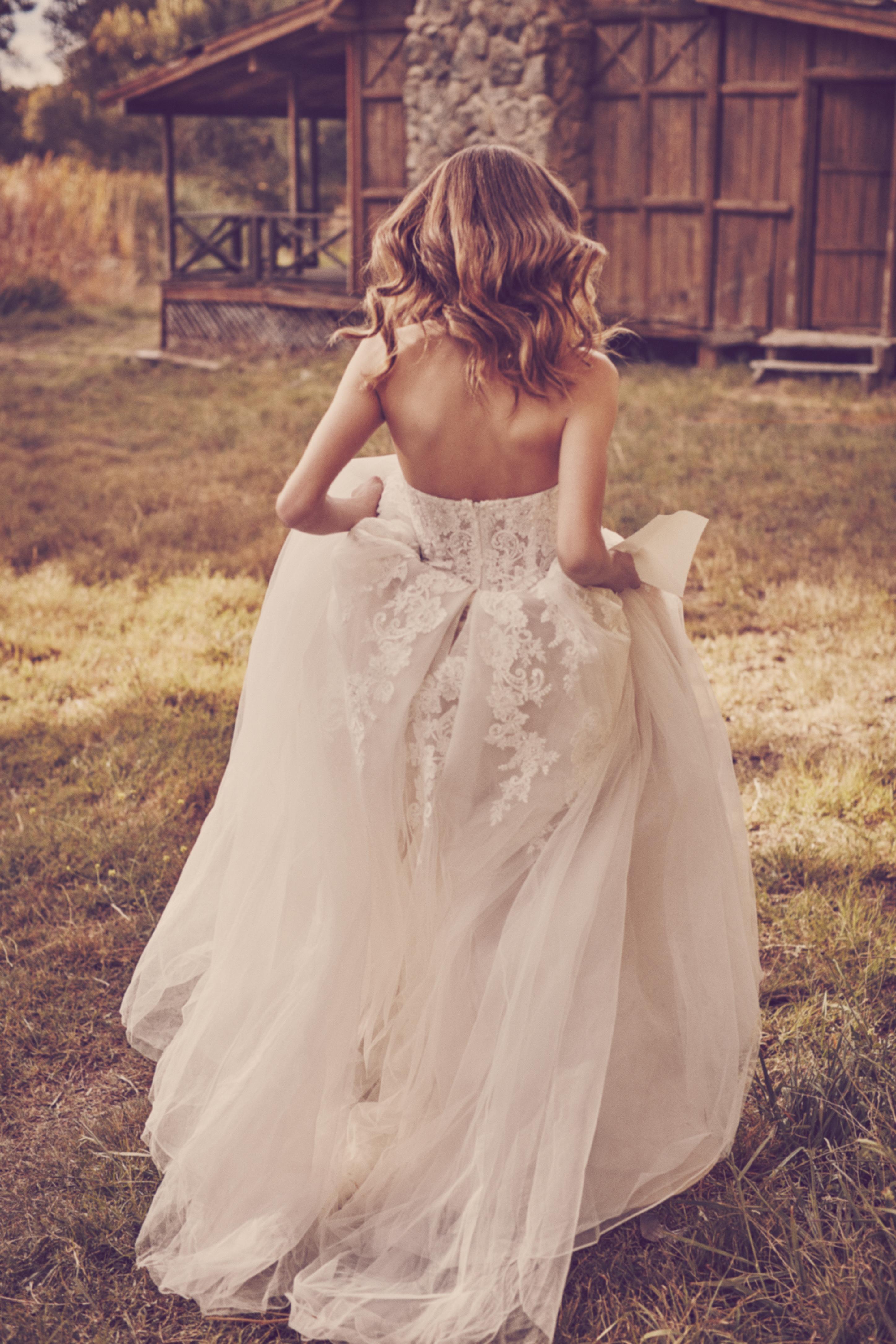 Woman running on grass holding up skirt of ball gown wedding dress