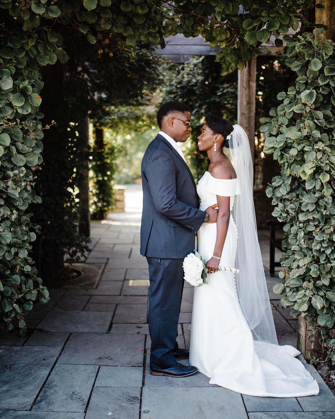 African American bride and groom standing under an archway covered in greenery.
