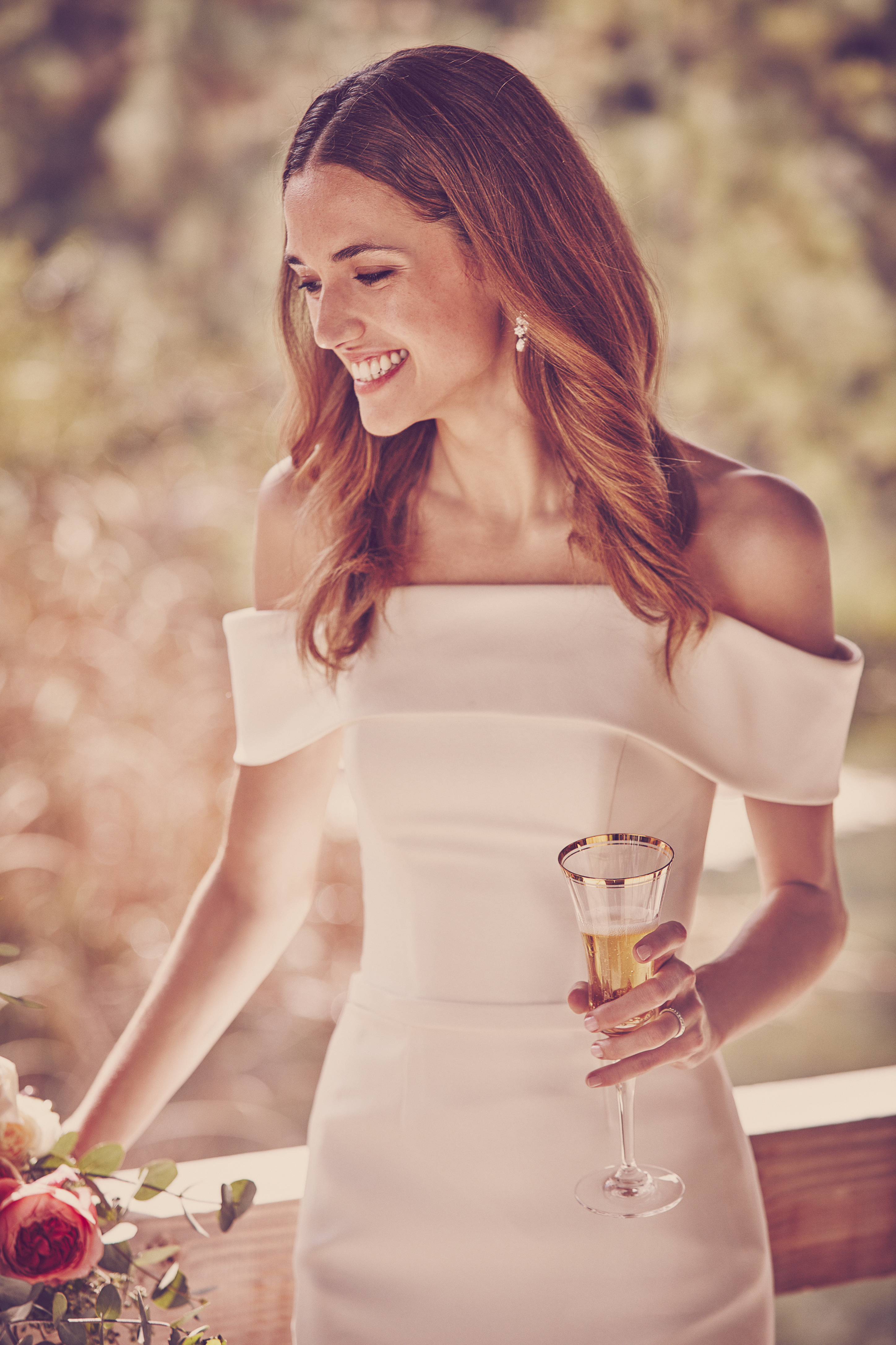 Woman in off-the-shoulder white wedding dress smiling and holding glass of champagne