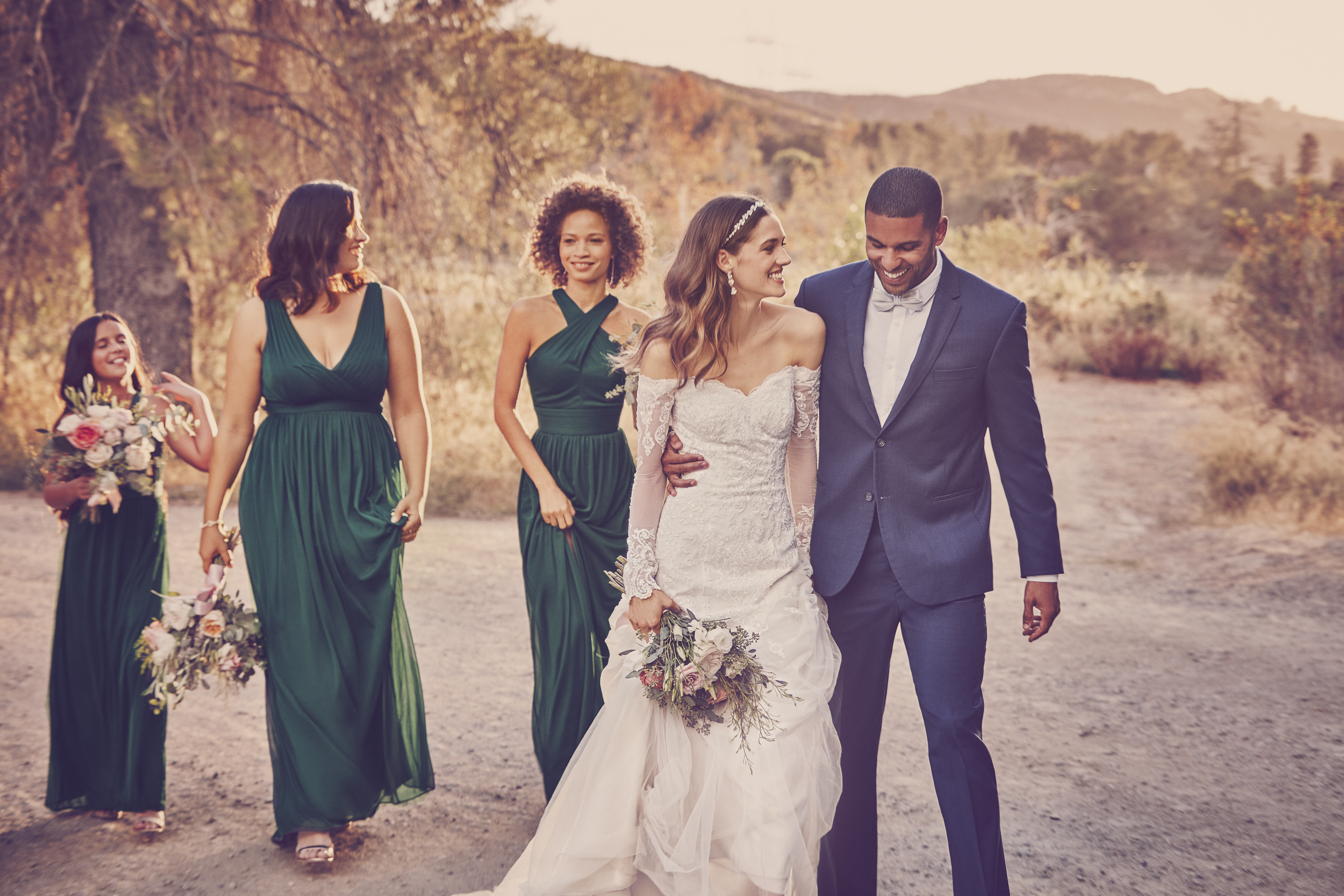 Man in suit, bride in white dress, and bridesmaids in green dresses walking on dirt road