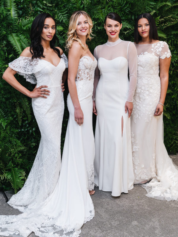 Four brides standing in front of greenery in white wedding dresses