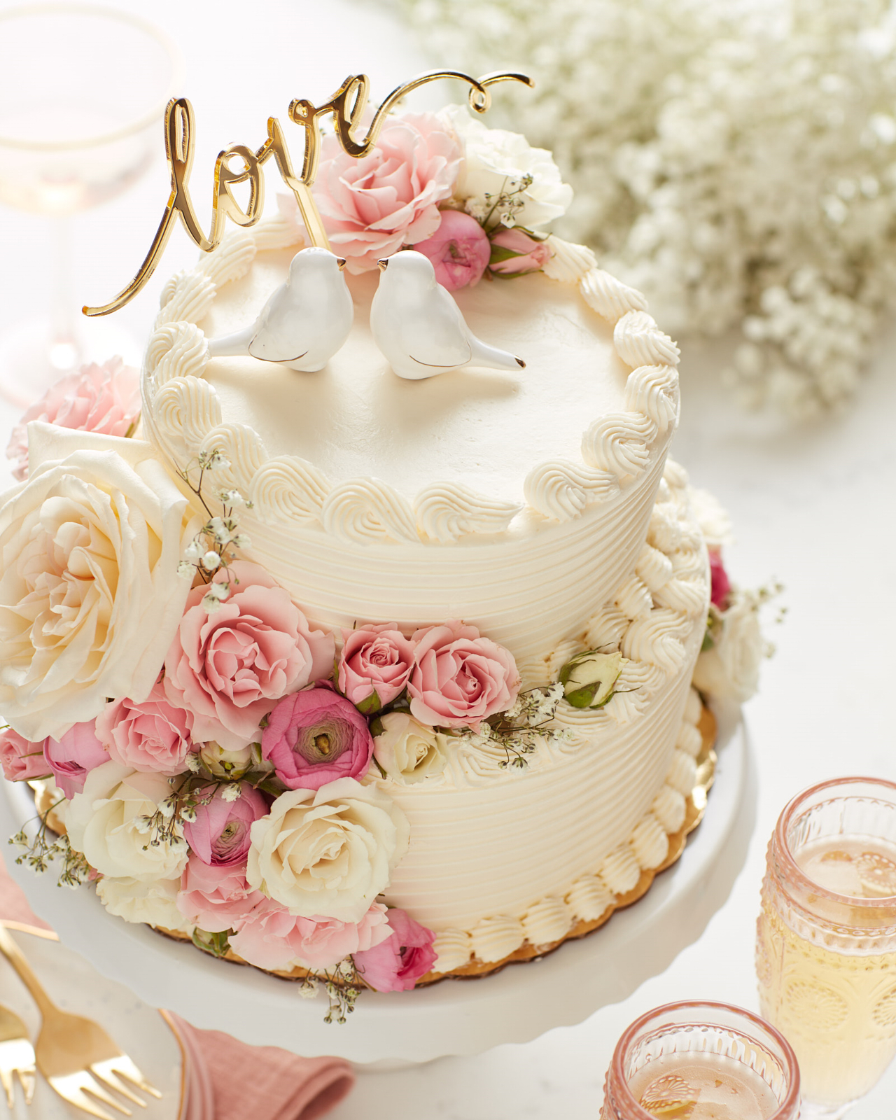 White two-tier wedding cake with pink and white flowers and a love script with two kissing birds cake topper