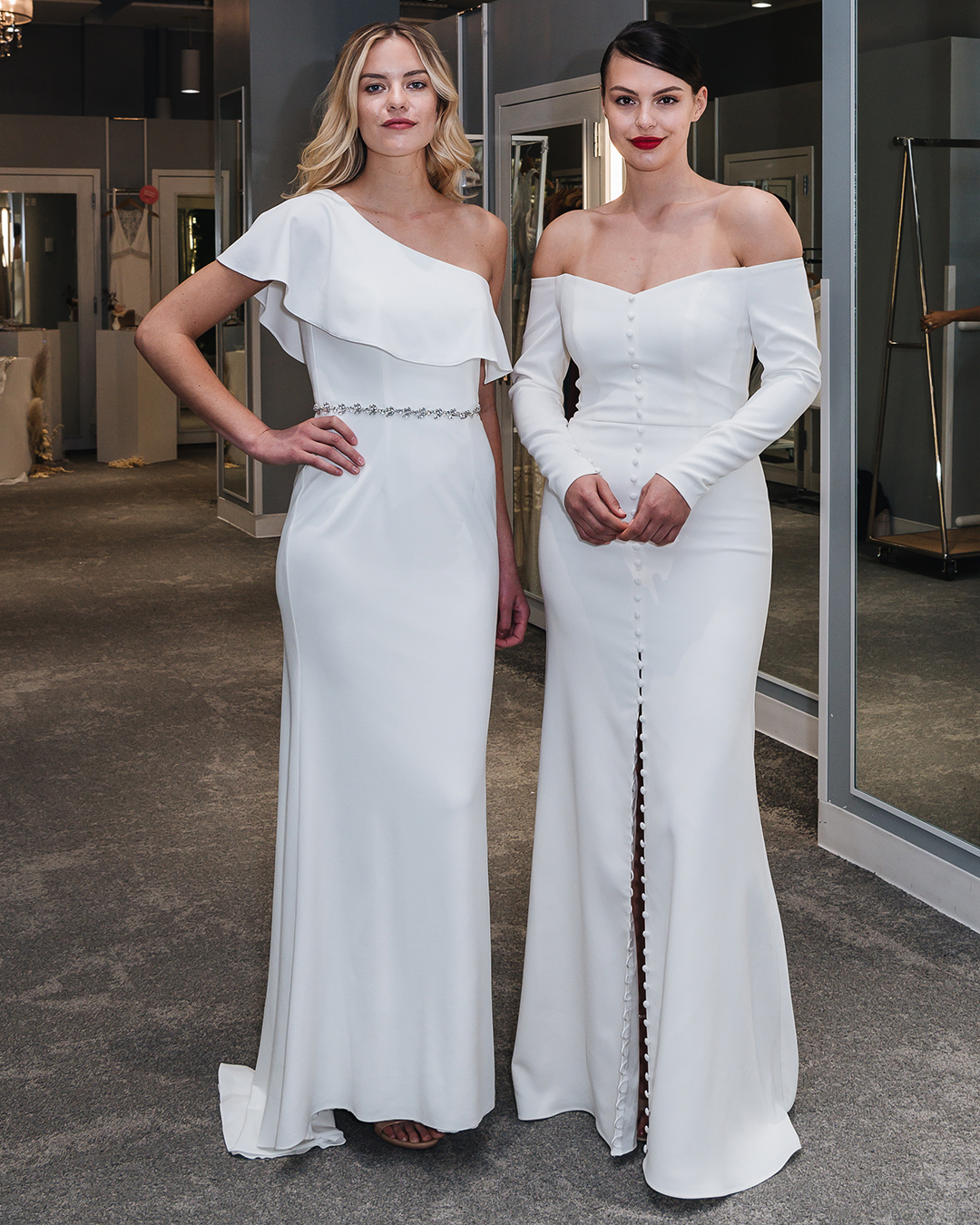 Two women standing in bridal store in modern white wedding dresses.